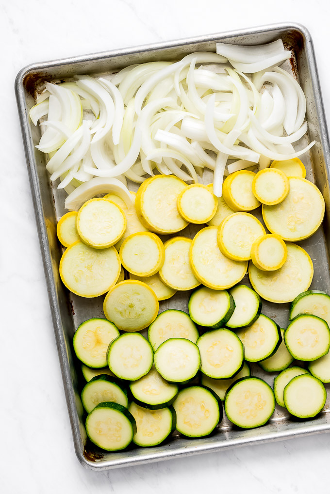 Onion, summer squash, and zucchini on a pan.