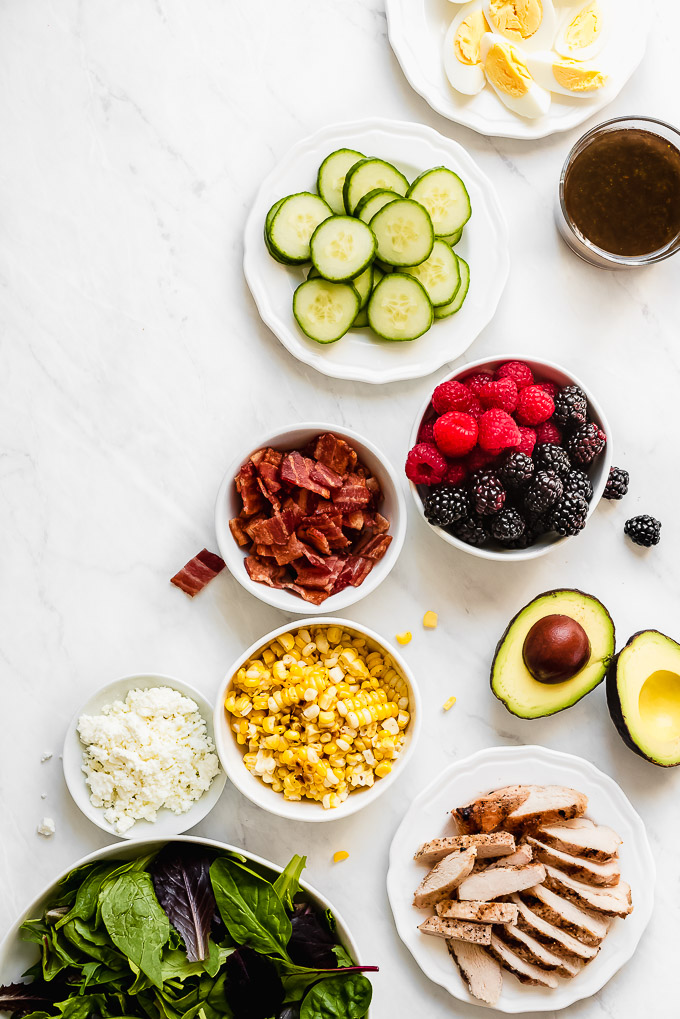 Ingredients for Summer Berry Cobb Salad- greens, grilled chicken, goat cheese, corn, avocado, bacon, berries, cucumbers, hard boiled eggs, and vinaigrette.