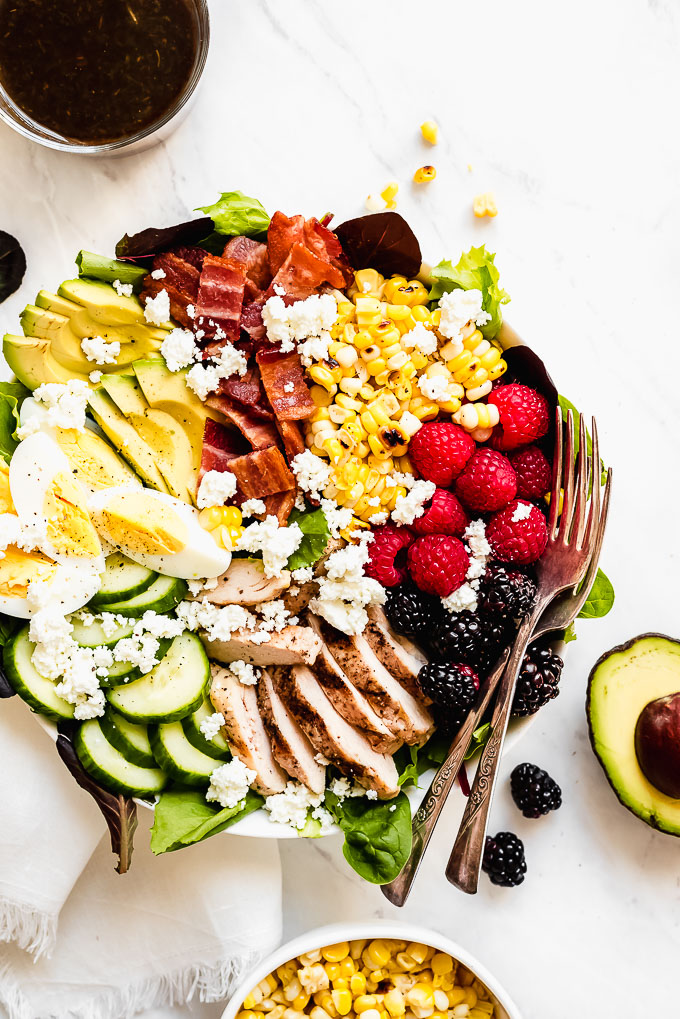 Colorful Summer Berry Cobb Salad in a bowl with a small bowl of balsamic vinaigrette to the side.