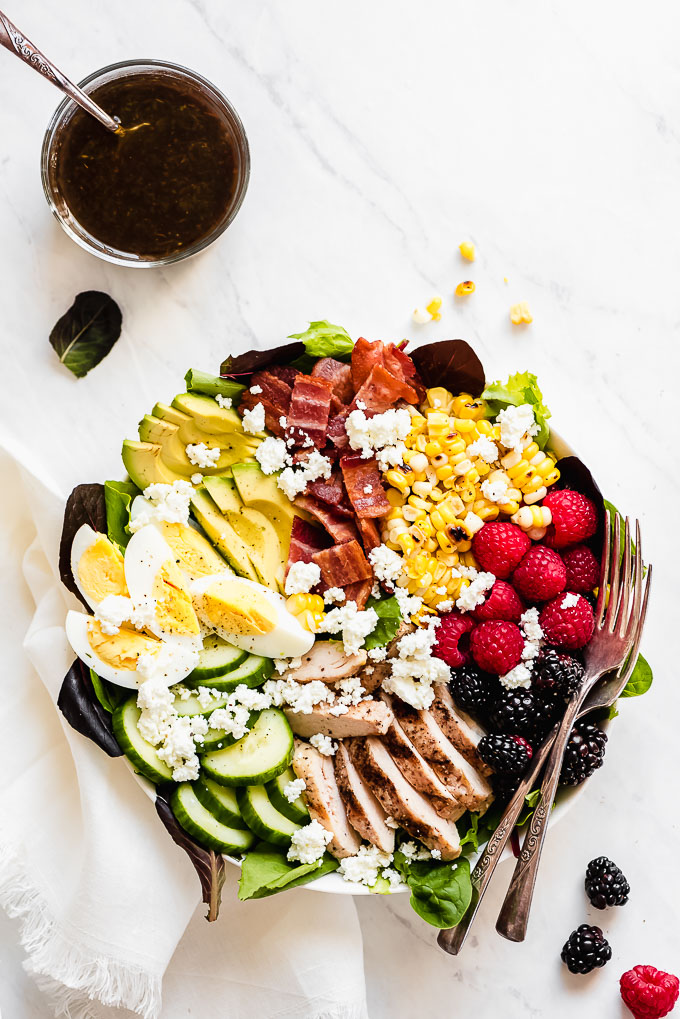 Bowl of Cobb Salad on a marble surface with forks on the side of the bowl.