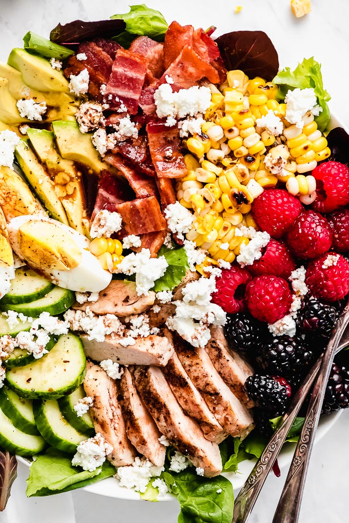 Close up view of Summer Berry Cobb Salad full of corn, berries, chicken, cucumbers, egg, avocado, bacon, and cheese.