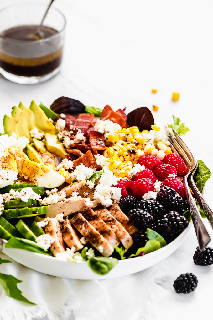 A white bowl full of Summer Cobb Salad and a small bowl of dressing in the background.