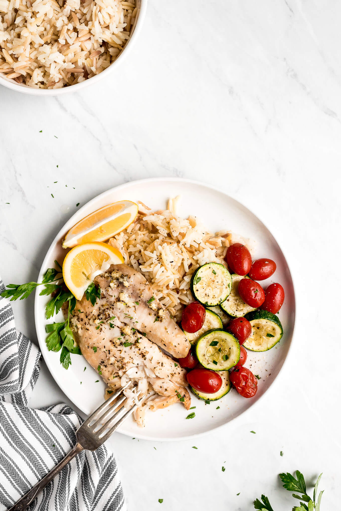 Baked Tilapia plated with zucchini, tomatoes, and orzo.
