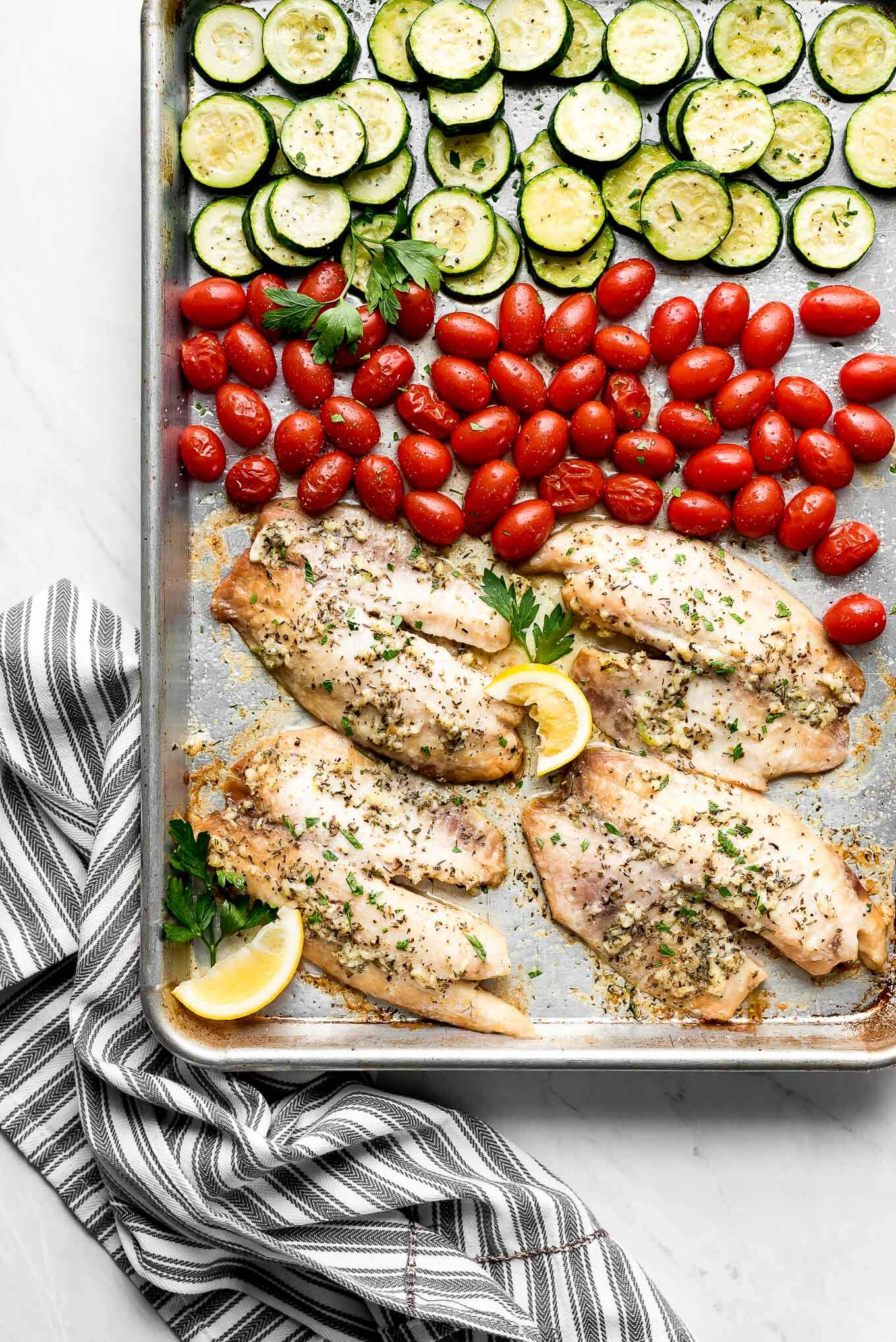 A sheet pan full of baked tilapia, tomatoes, and zucchini.