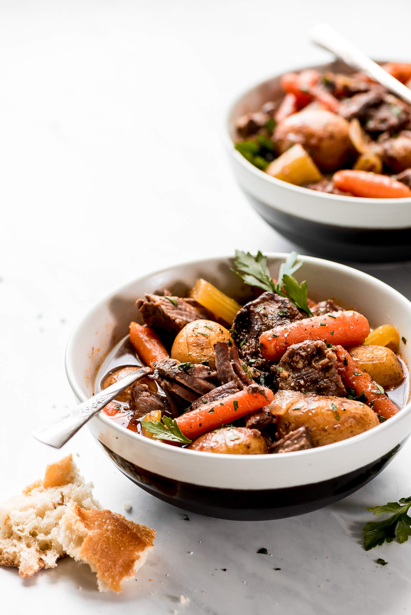 A bowl of fall-apart tender beef, carrots, potatoes, celery, and onion.