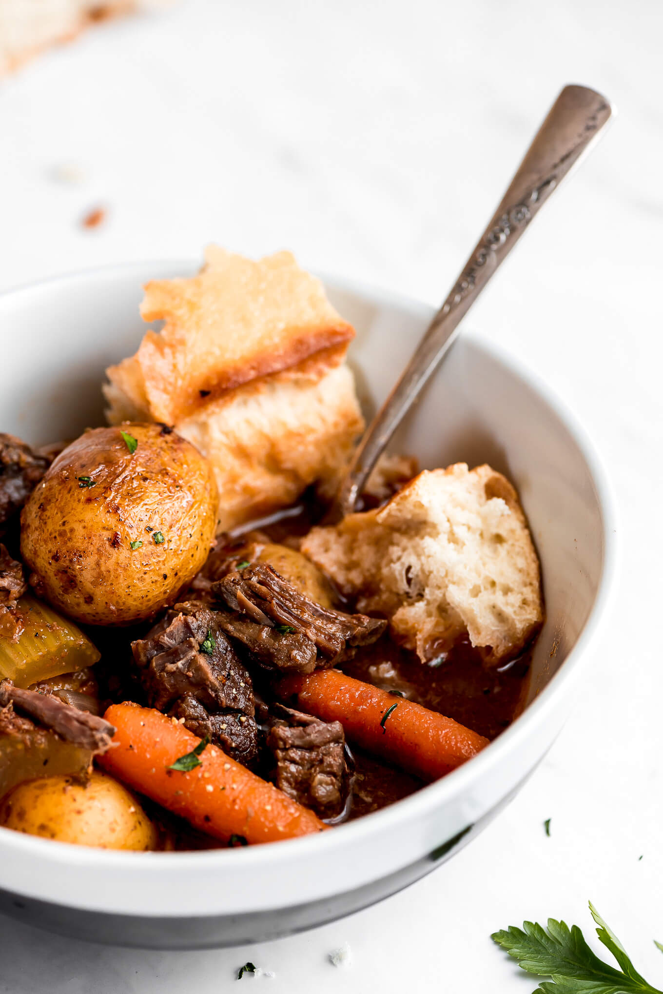 A close up of a bowl of tender, fall-apart beef, potatoes, carrots, and french bread.