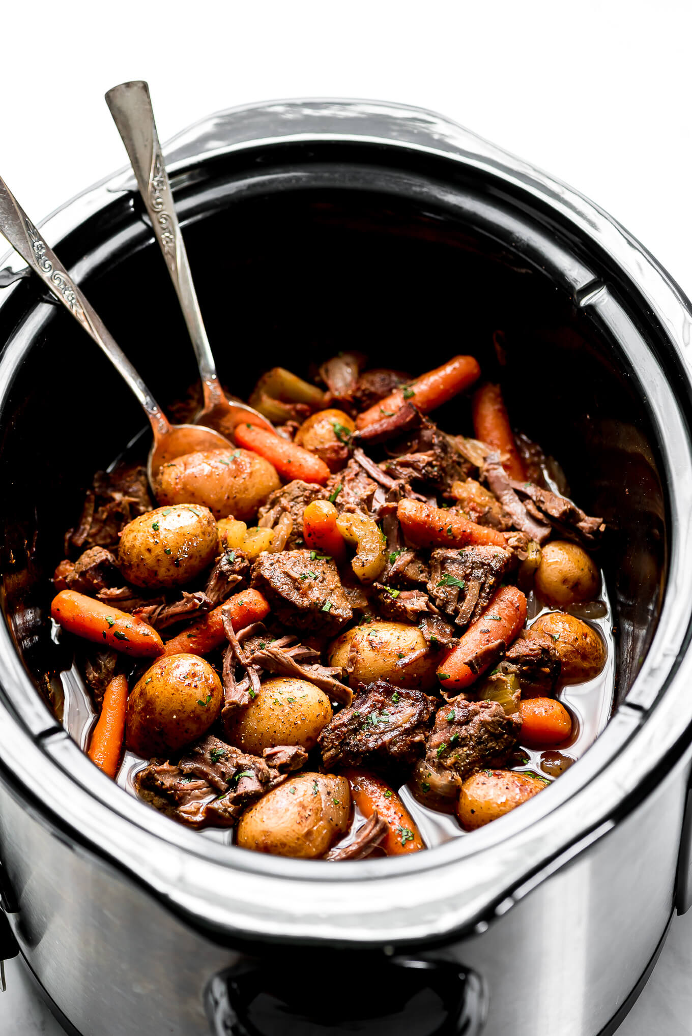 Slow Cooker Beef Stew in a Crock-Pot with two spoon resting in the bowl.