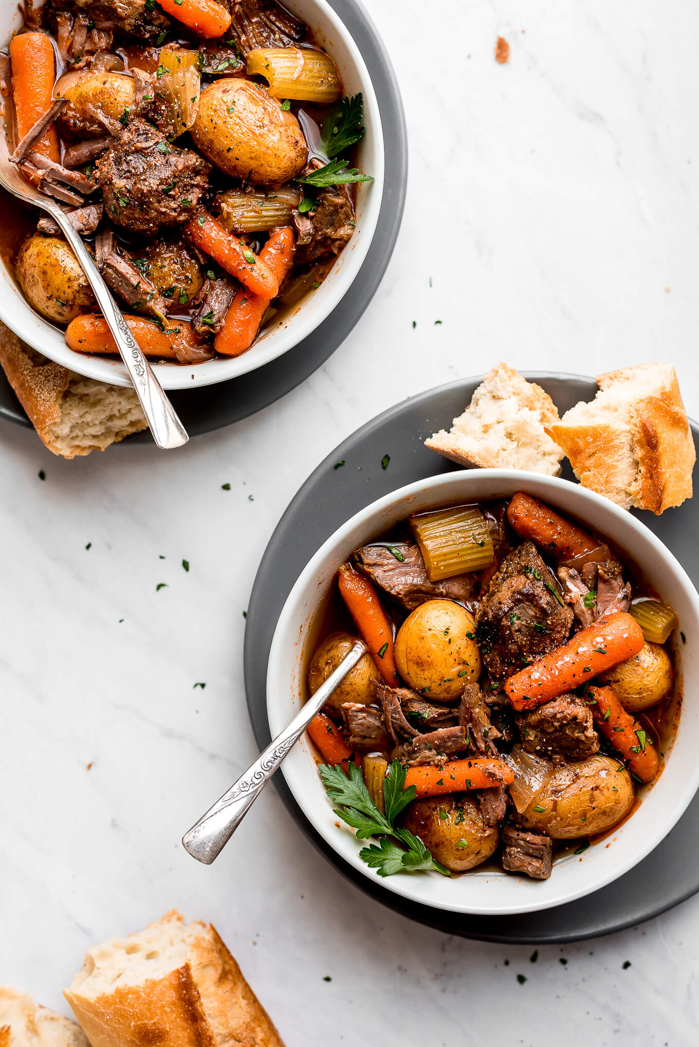 Two bowls of the best beef stew on plates with french bread at the side.