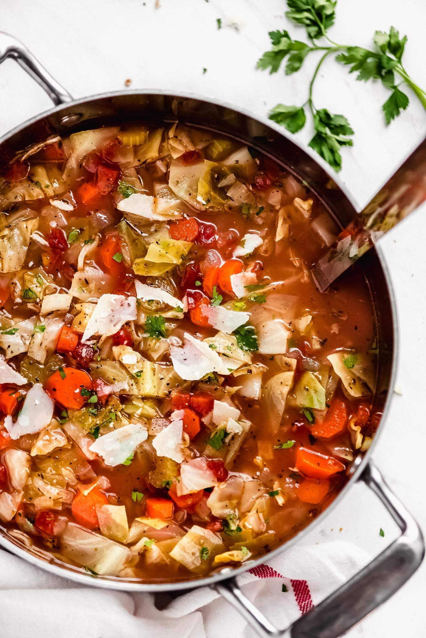 A large pot of Cabbage Soup with shaved Parmesan and chopped parsley sprinkled on top.
