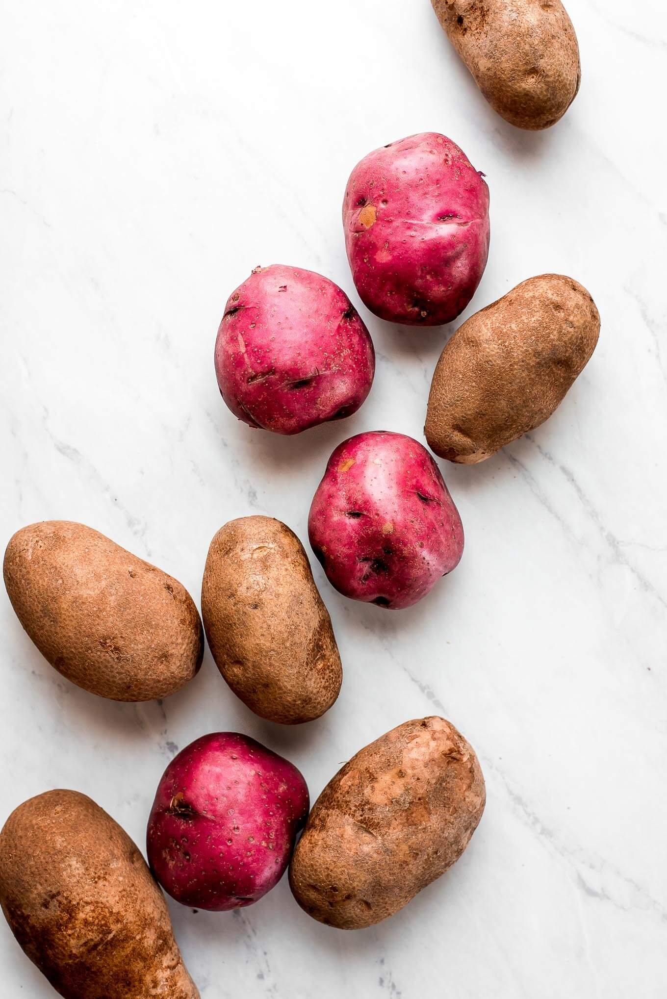 Russet potatoes and red potatoes on a marble surface.