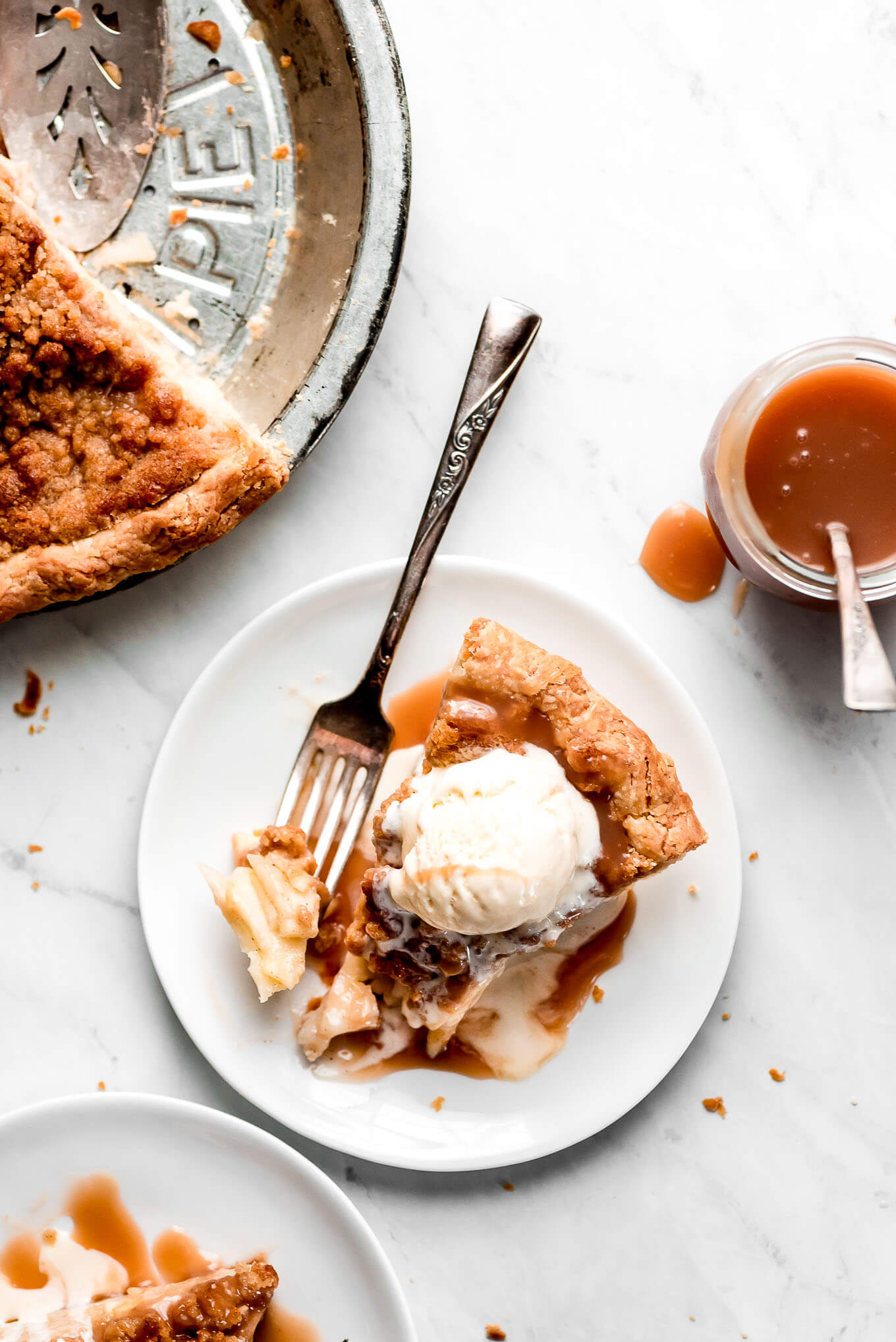 A slice of Apple Pie topped with ice cream and caramel sauce with a jar of caramel to the side.