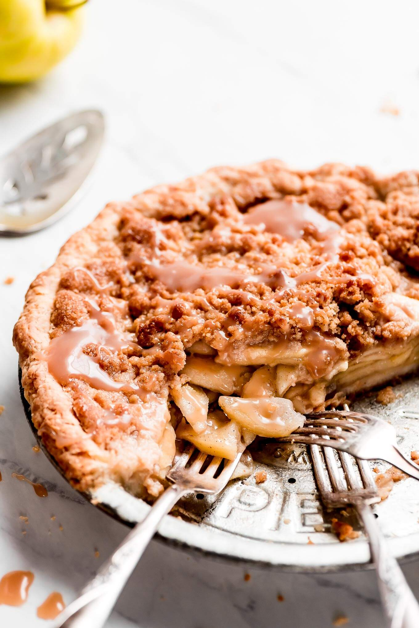 A close up shot of the inside of an Apple Crumble Pie in a pie dish with caramel sauce drizzled over it.