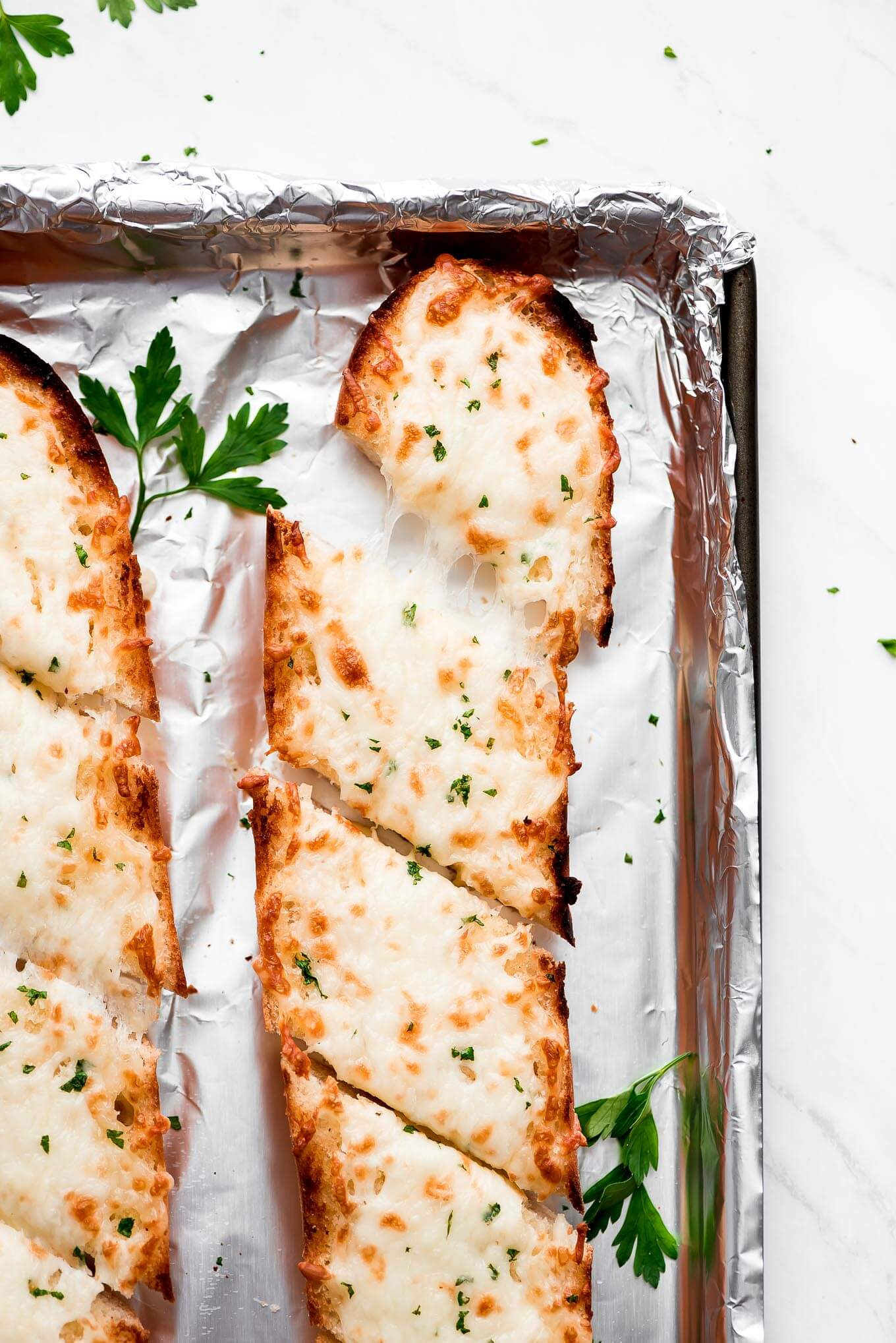 Garlic Bread on a foil lined baking sheet and sliced at an angle into individual portions.