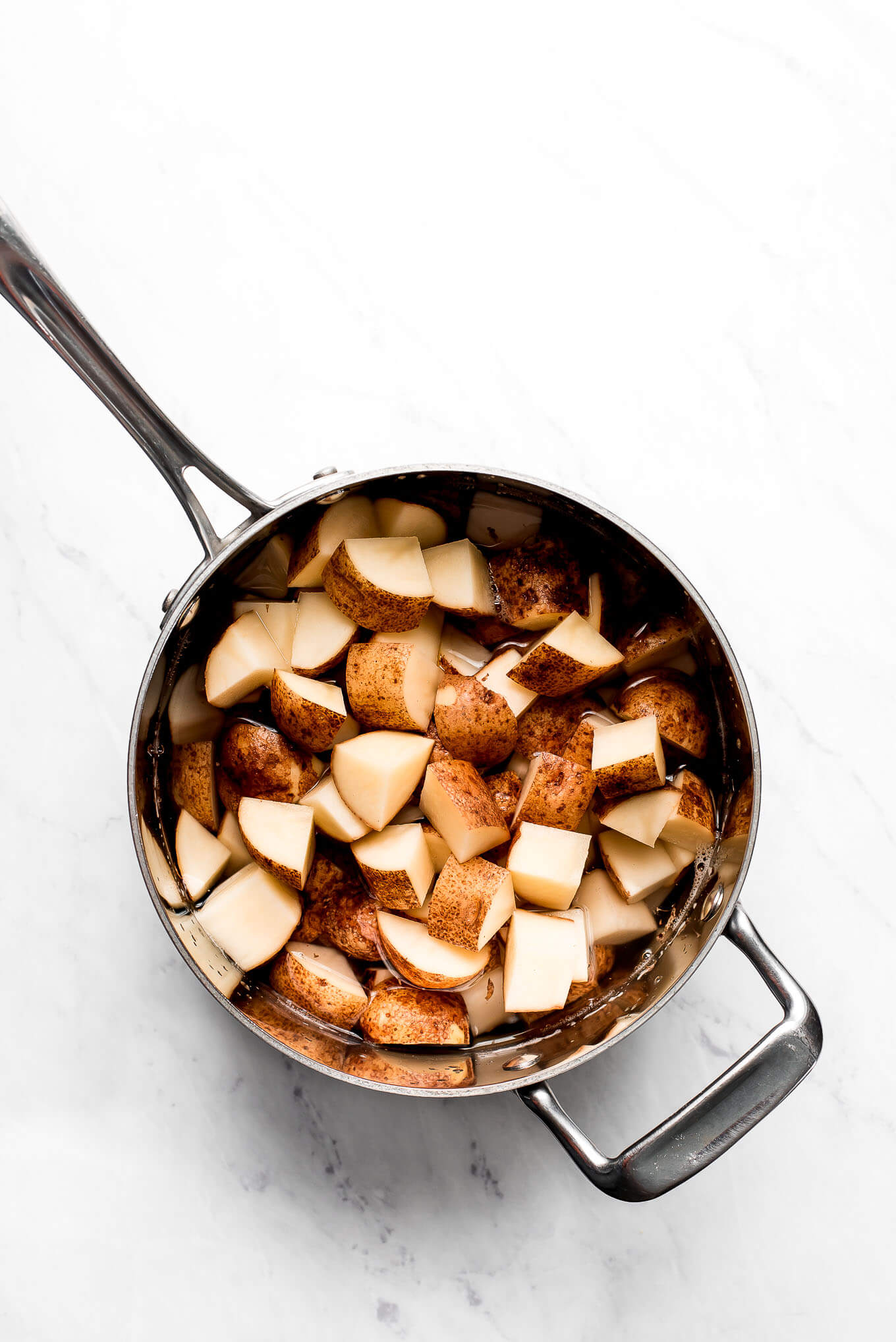Cut up russet potatoes with the skin on in a pot of water.