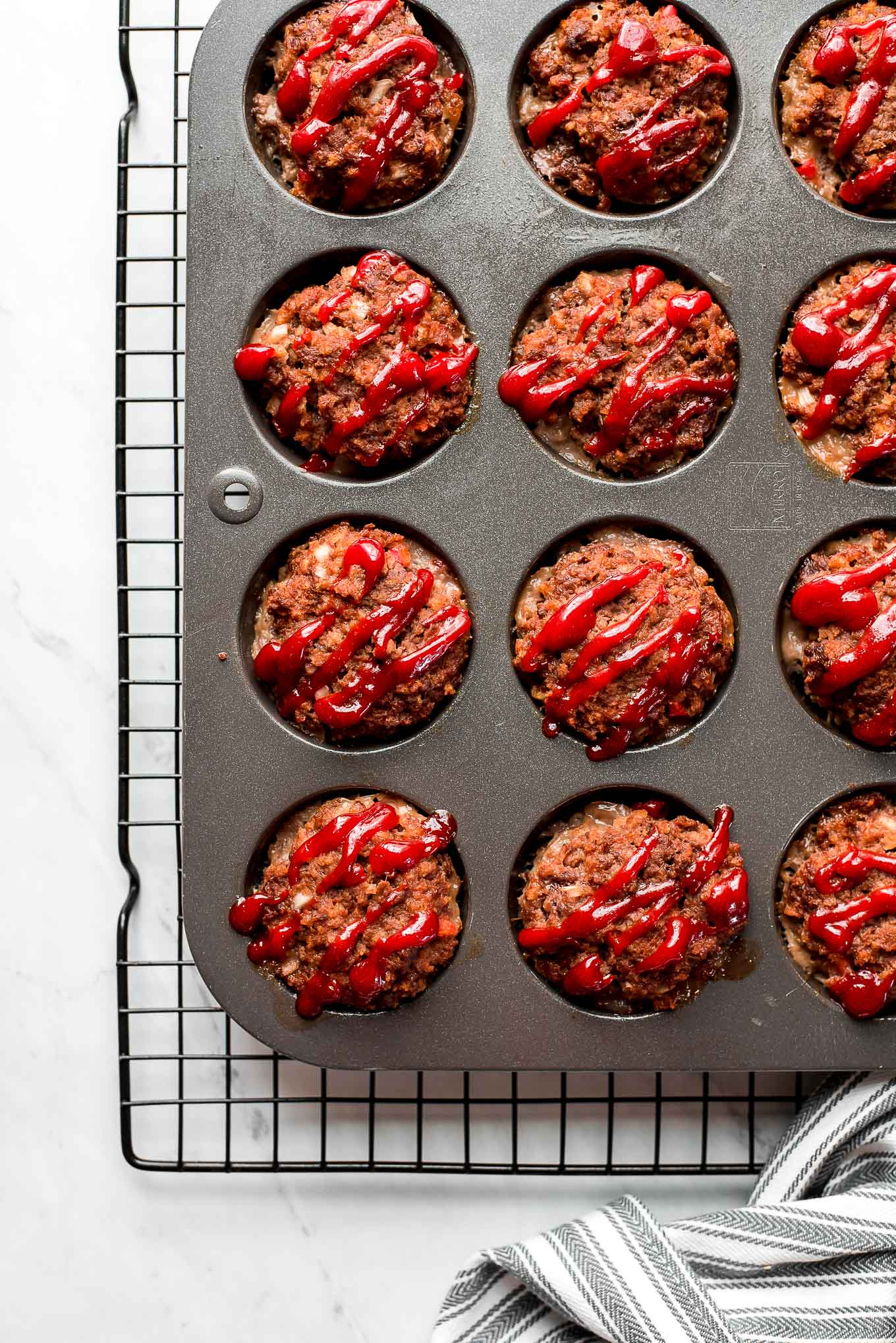 Meatloaf muffins drizzled with ketchup and in a muffin tin.
