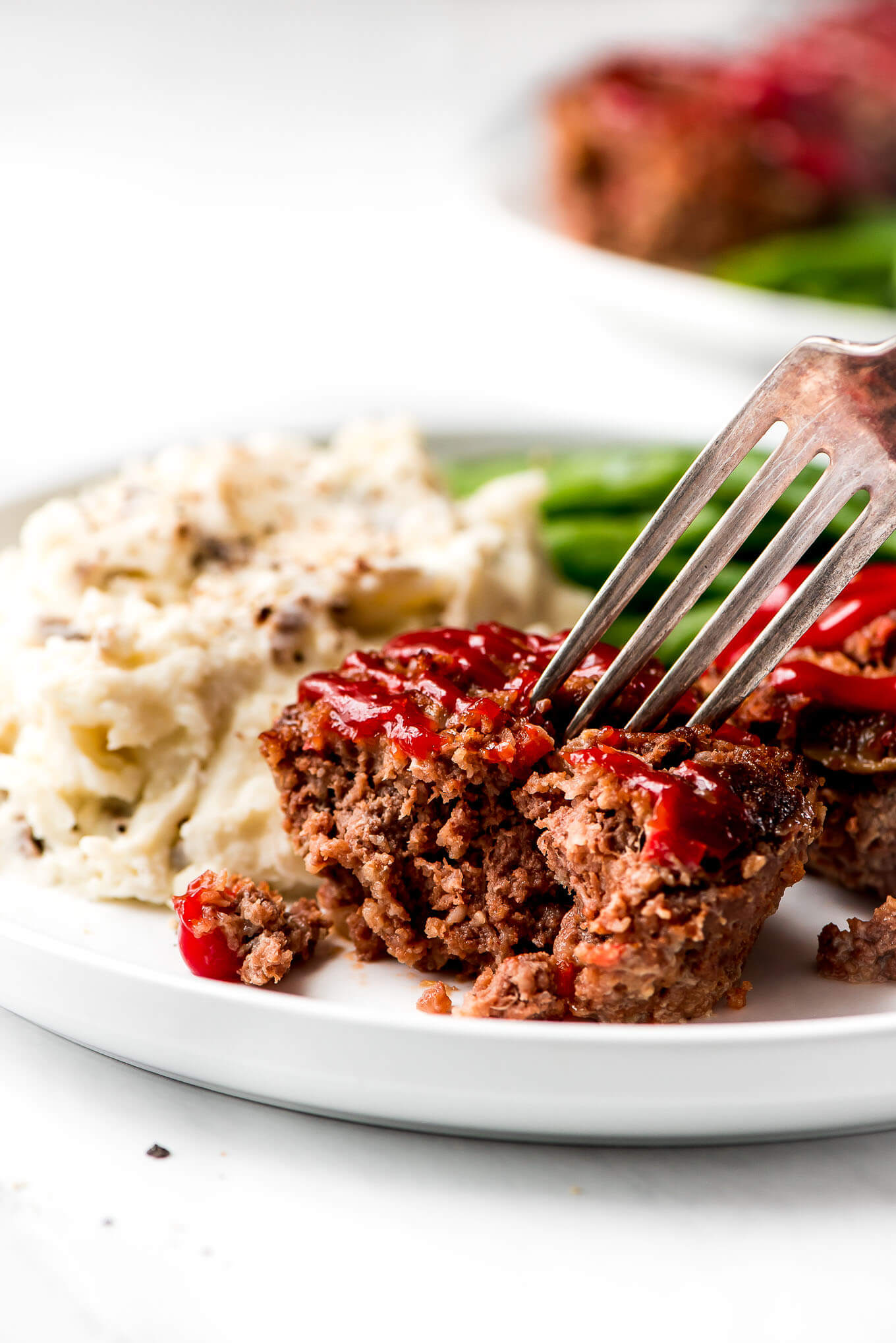 Half of a Mini Meatloaf showing the inside and a fork cutting into it.