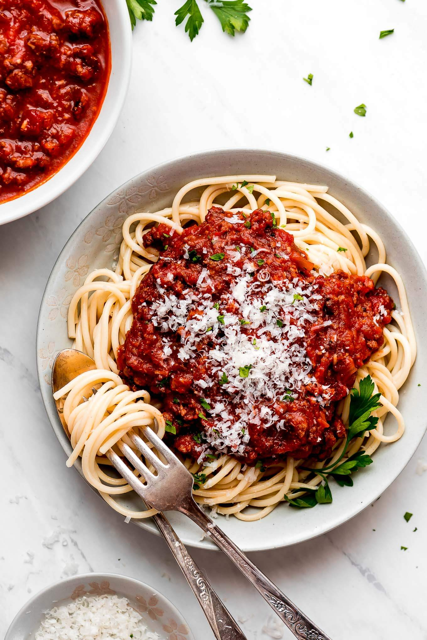 Spaghetti Meat Sauce on top of spaghetti noodles in a bowl with noodles twisted around a fork.