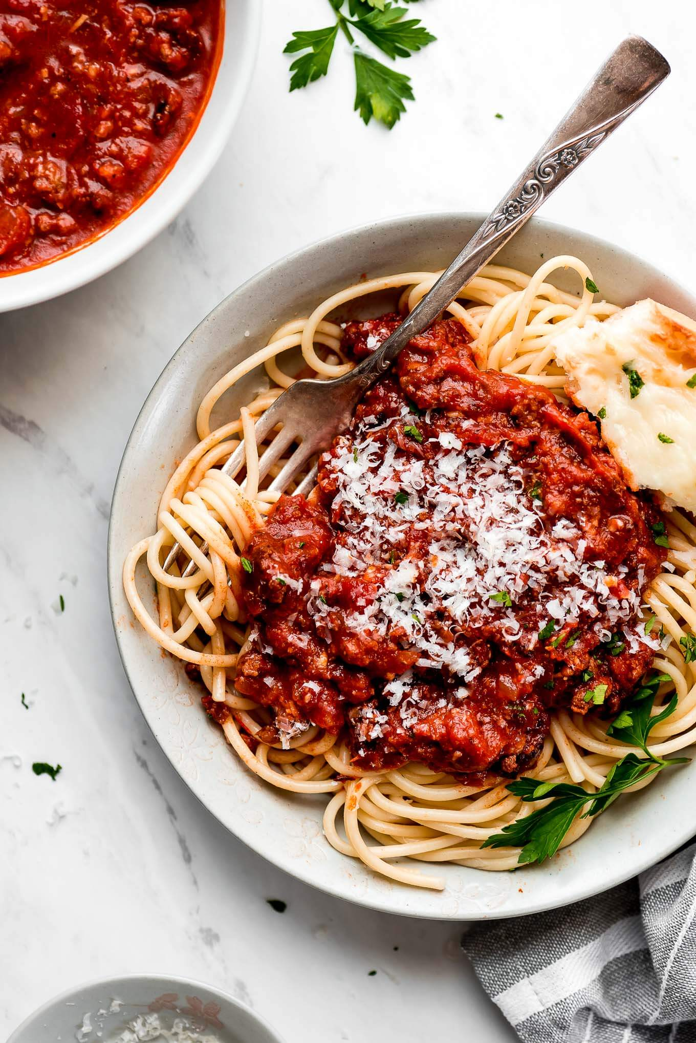 A bowl of spaghetti topped with homemade spaghetti sauce and Parmesan cheese.