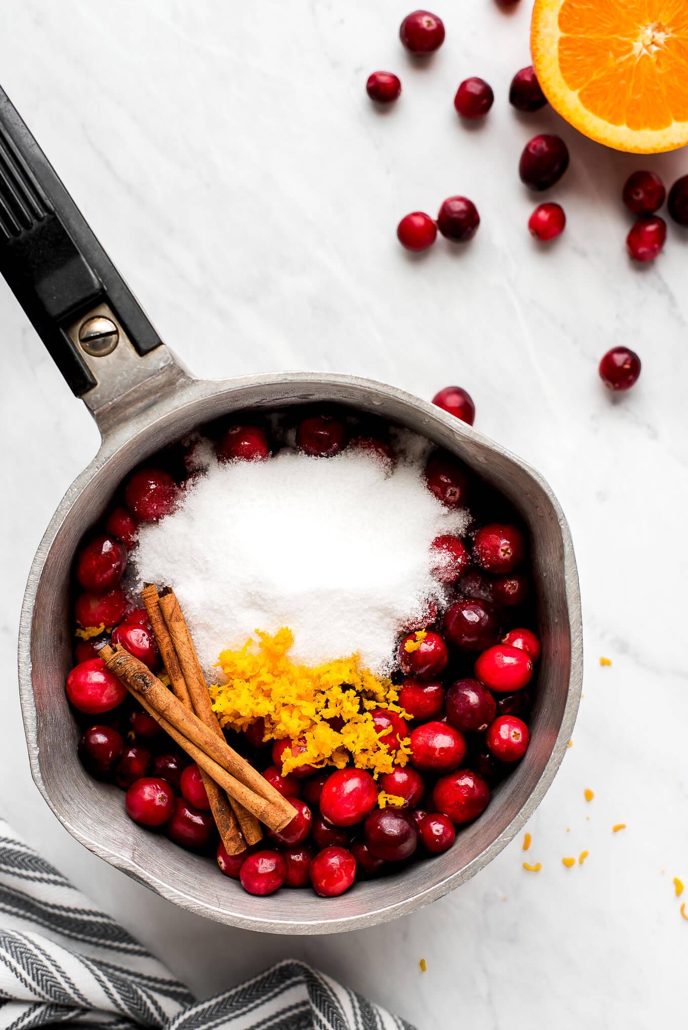 Cranberries, sugar, orange zest, and cinnamon sticks in a pot.
