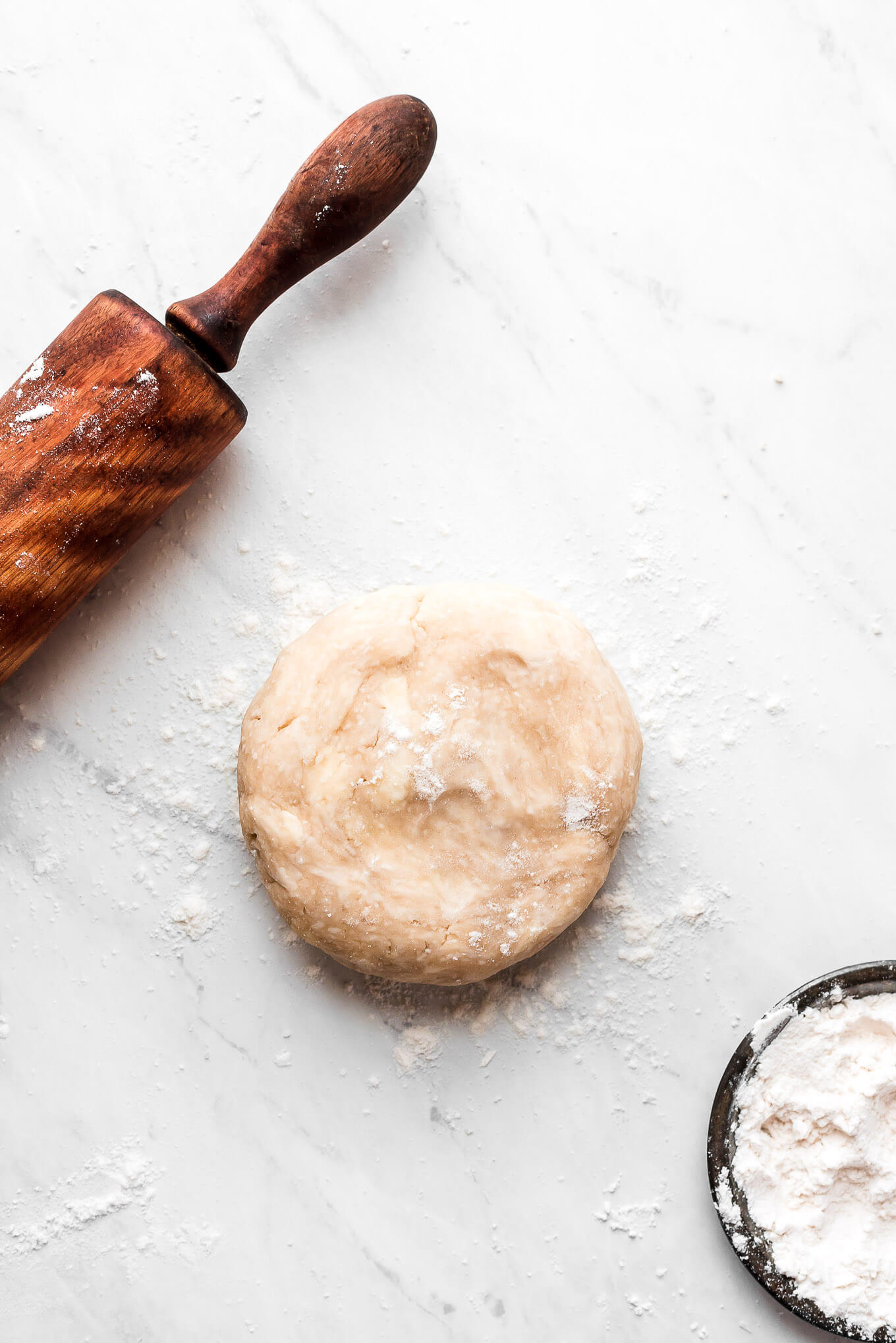 Pie dough, a rolling pin, and a dish of flour.