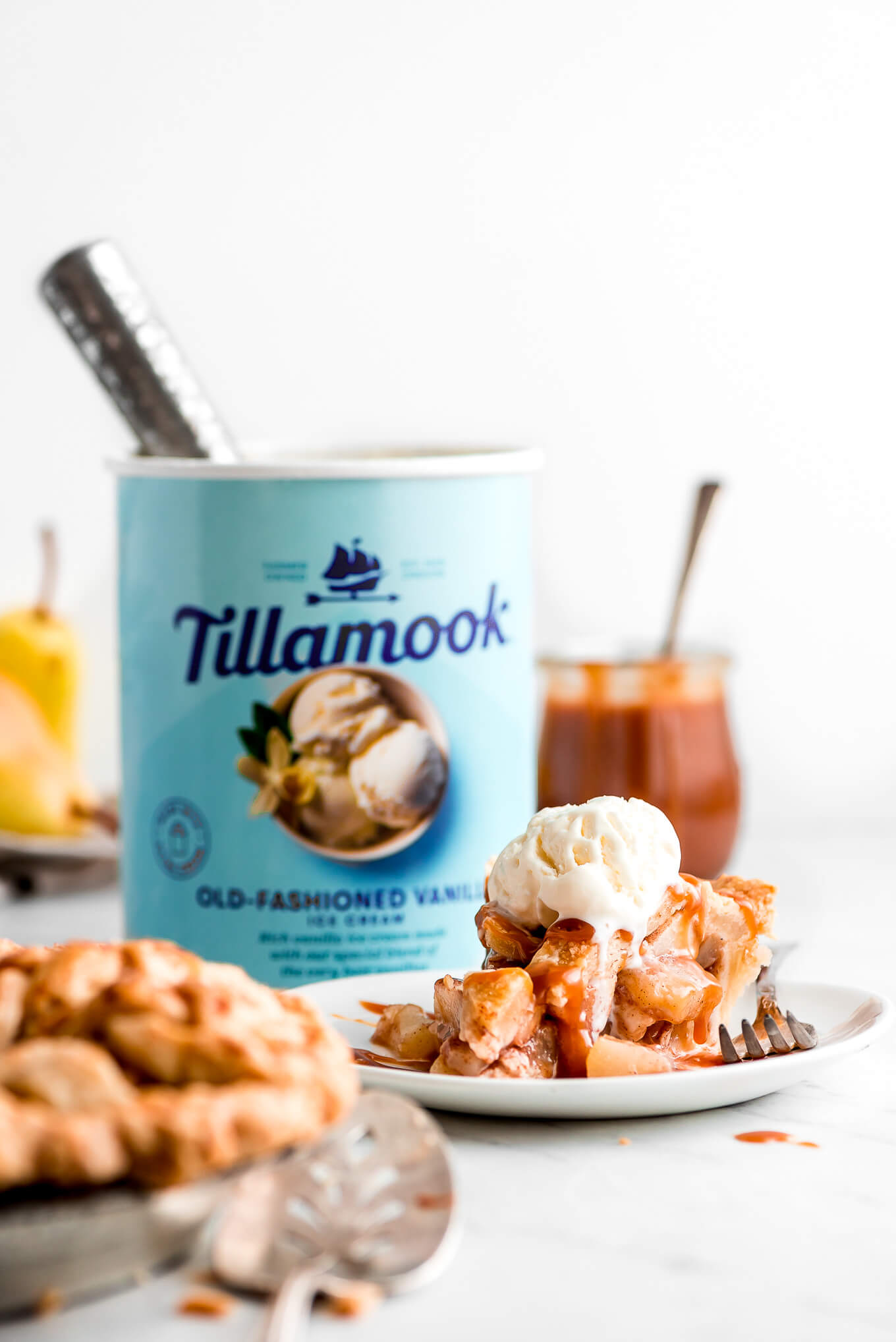 A slice of pie on a plate with ice cream on top and a carton of Tillamook Vanilla Ice Cream in the background.