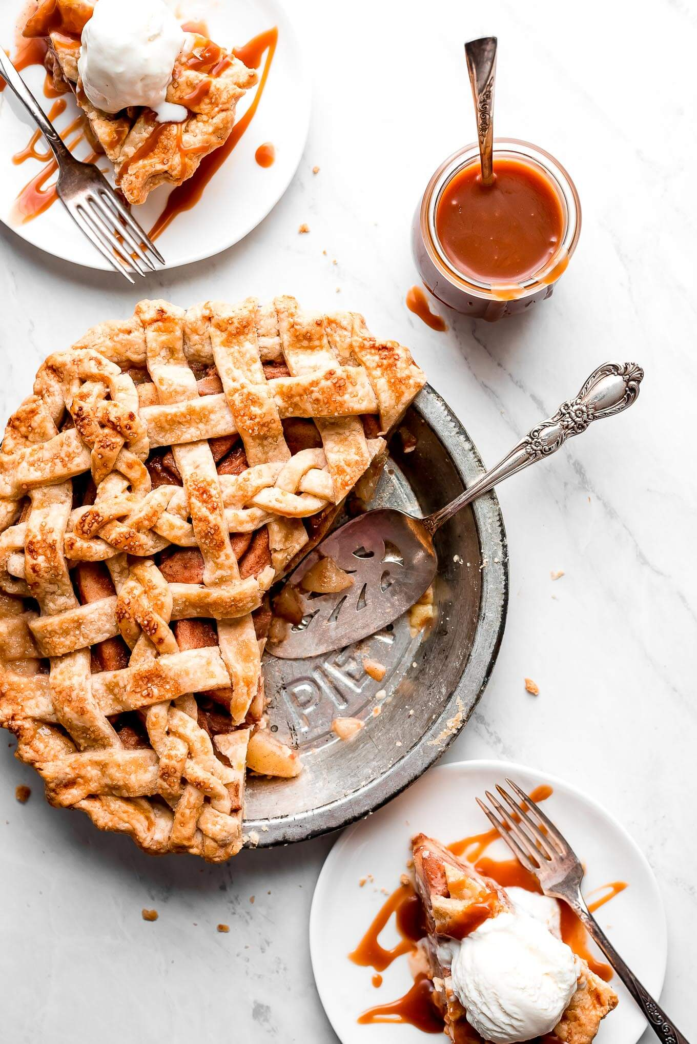A Pear Pie with a lattice top, two slices cut out of it and on plates, drizzled with caramel and topped with ice cream.