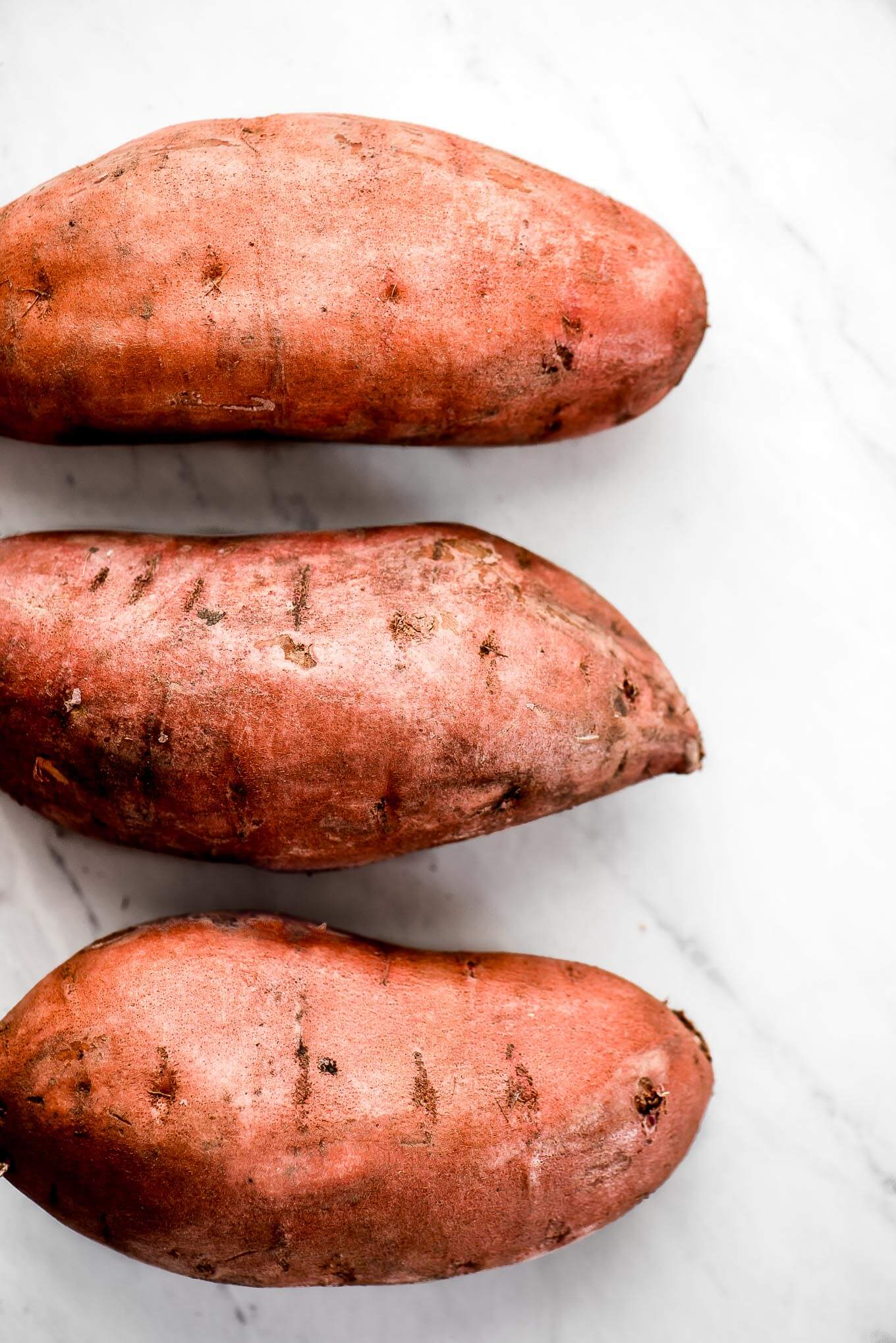 Three raw sweet potatoes.