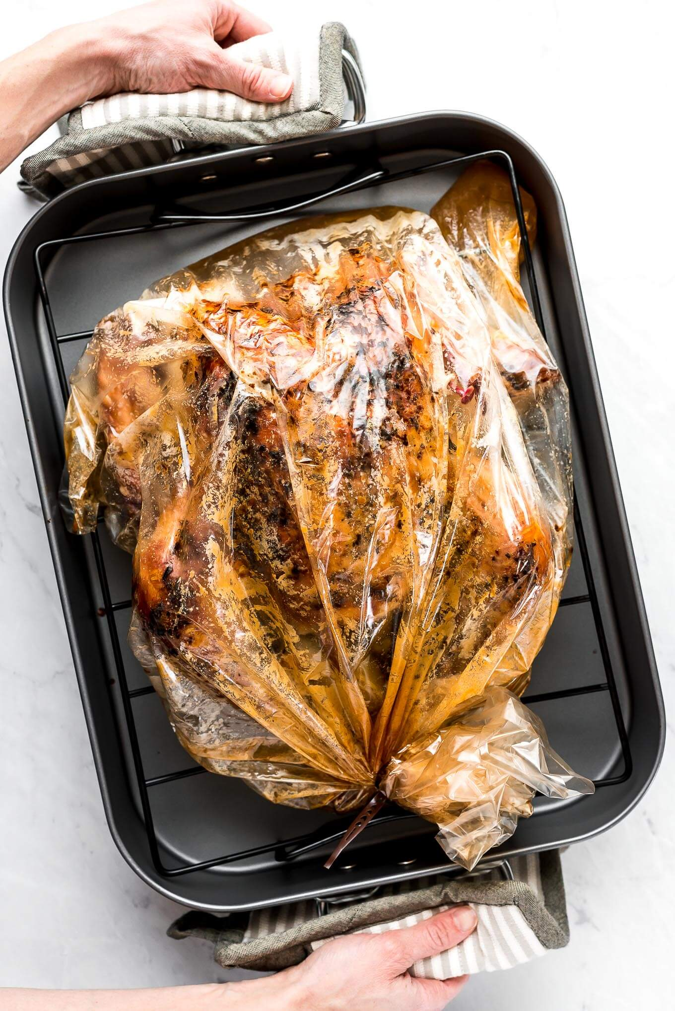 A roasting pan with cooked turkey in a bag and hands holding hot pads on the handles.