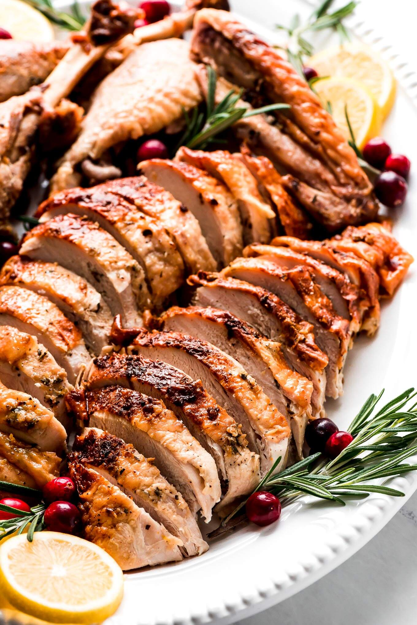 Roast Turkey in a Bag sliced up on a platter garnished with cranberries, rosemary, and lemon slices