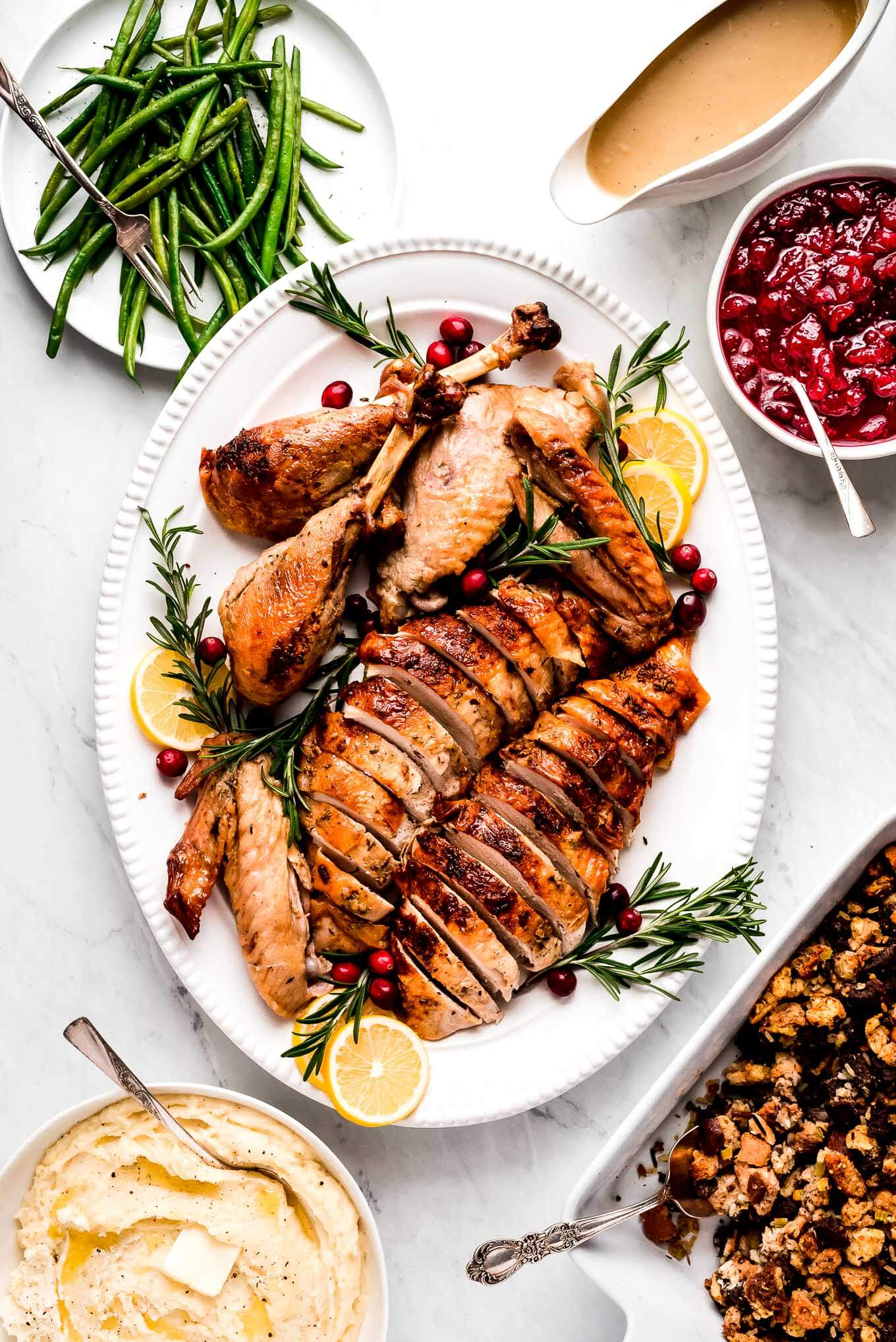 Roast Turkey in a Bag cut up and on a platter with serving bowls of green beans, mashed potatoes, stuffing, gravy, and cranberry sauce around it.