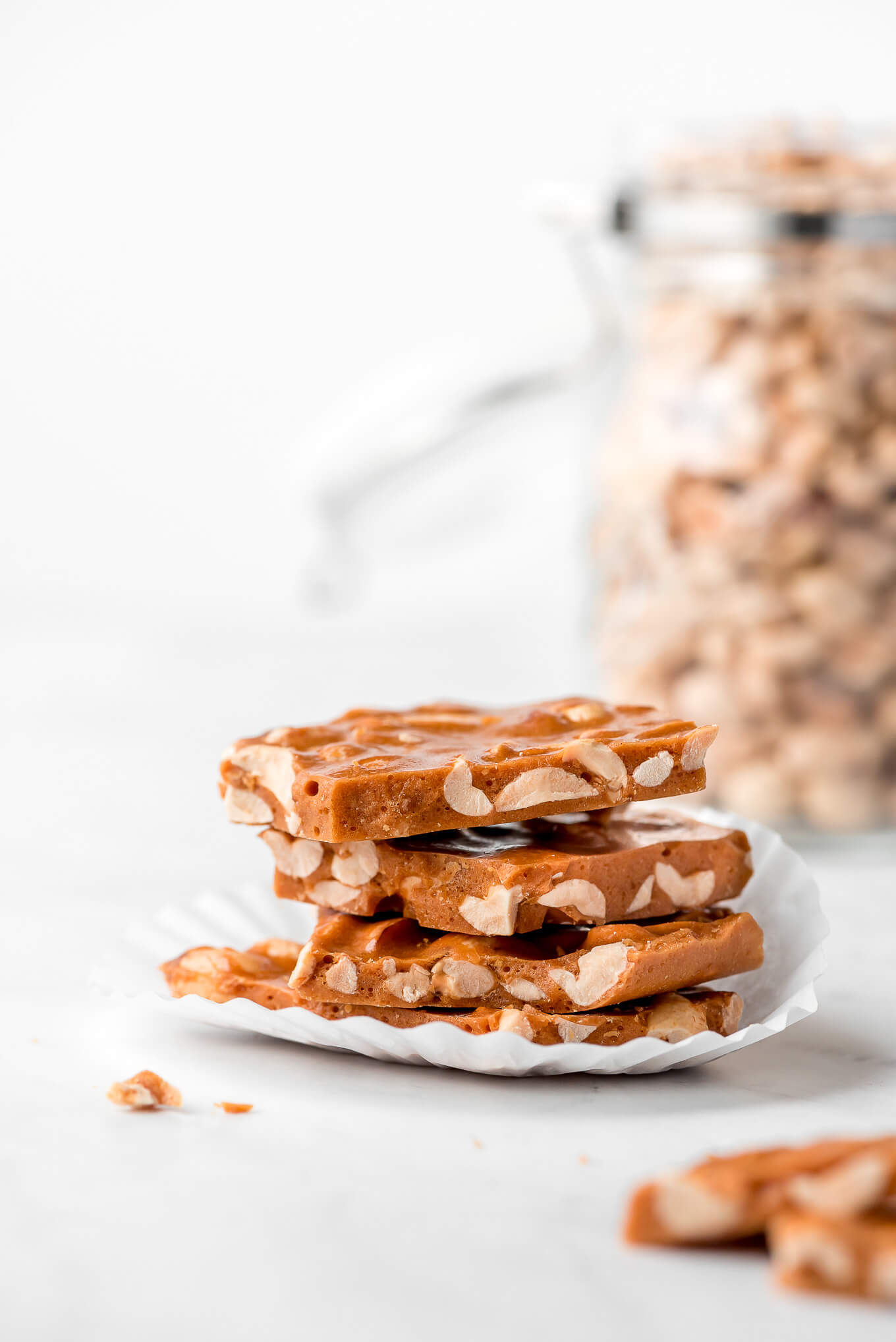 Pieces of Peanut Brittle stacked on top of each other on a cupcake paper liner and a jar of peanuts in the background.