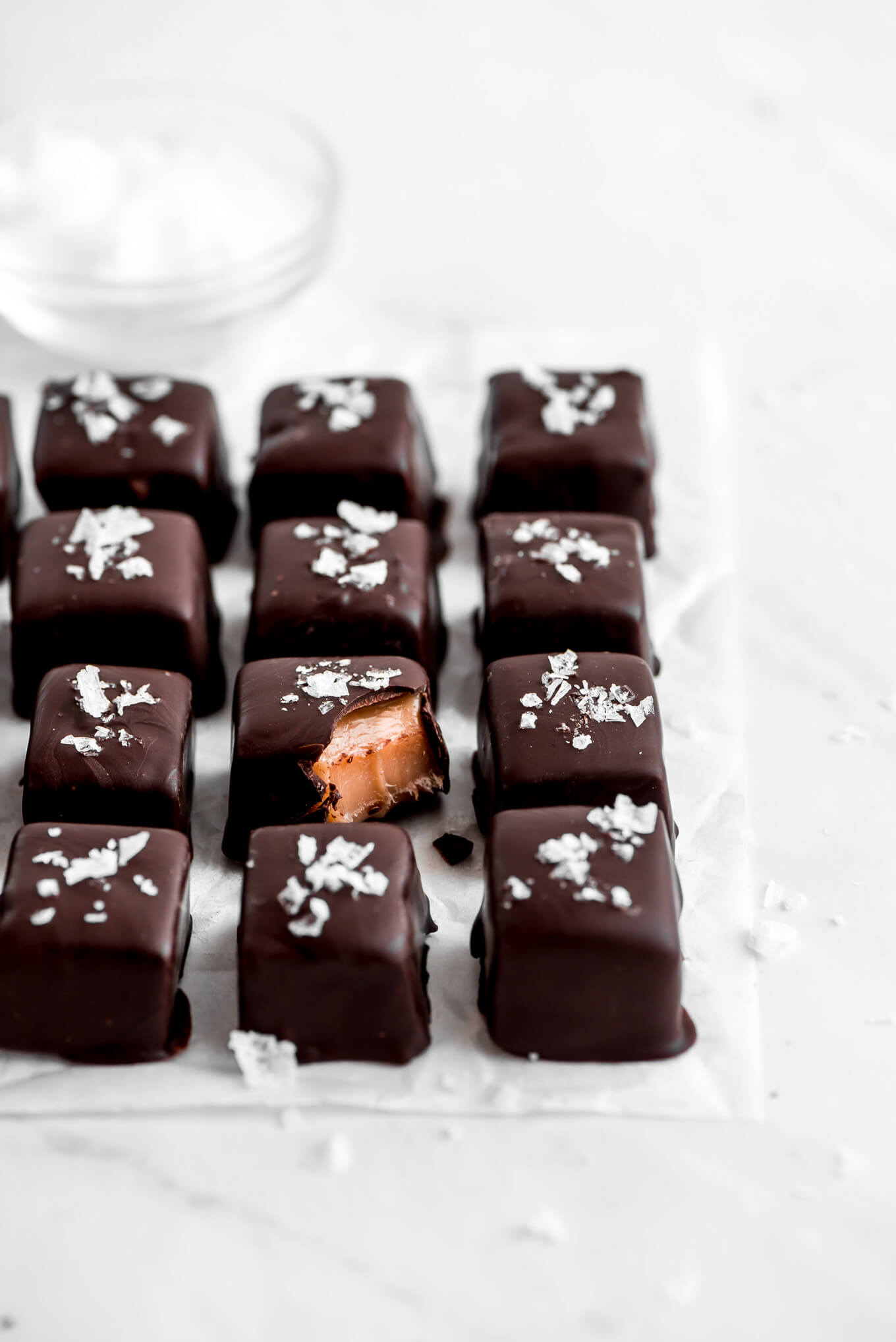 Chocolates with sea salt on top in rows on a parchment paper.