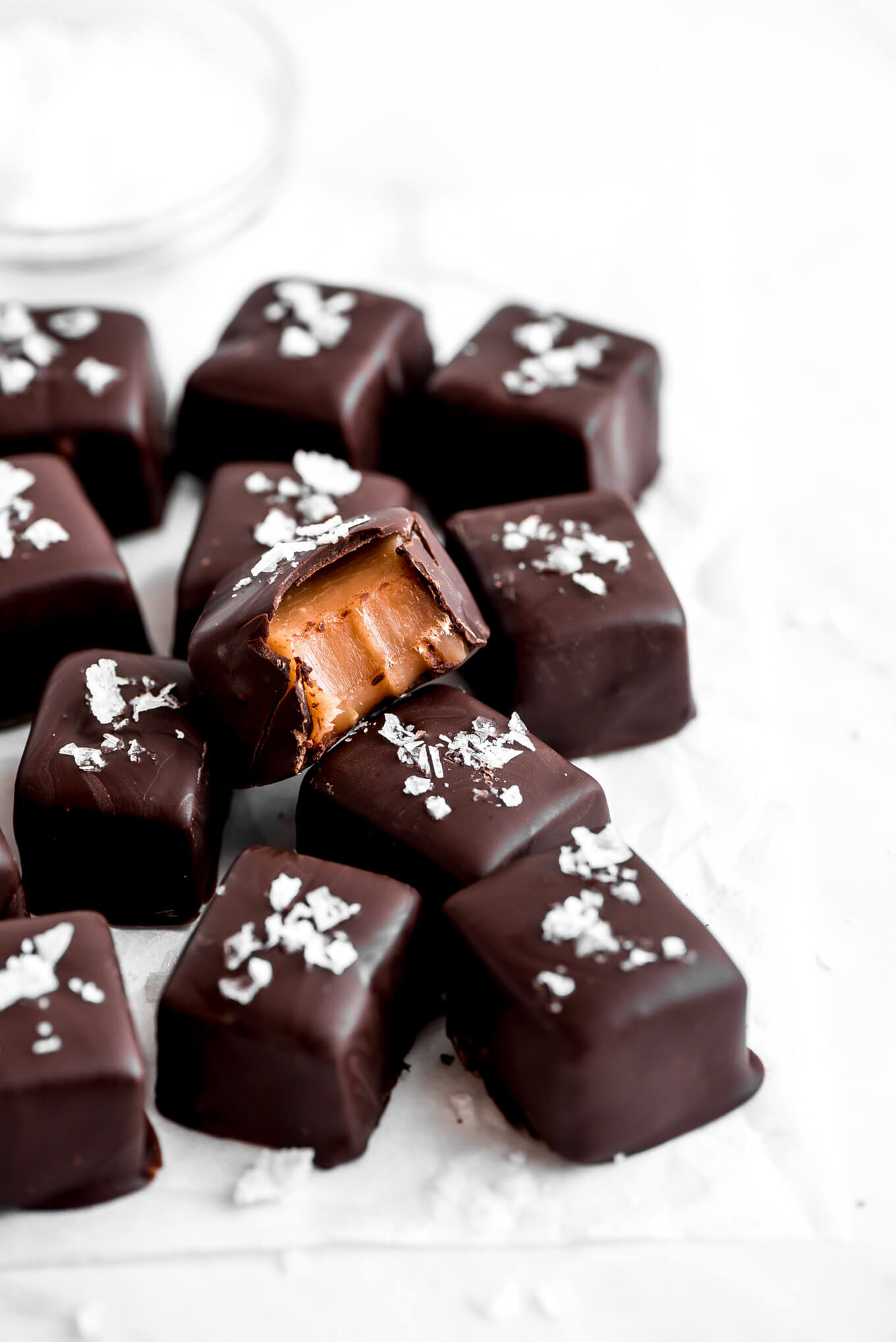Several chocolate coated caramels with sea salt on top and one of them with a bite taken out of the corner showing the caramel inside.