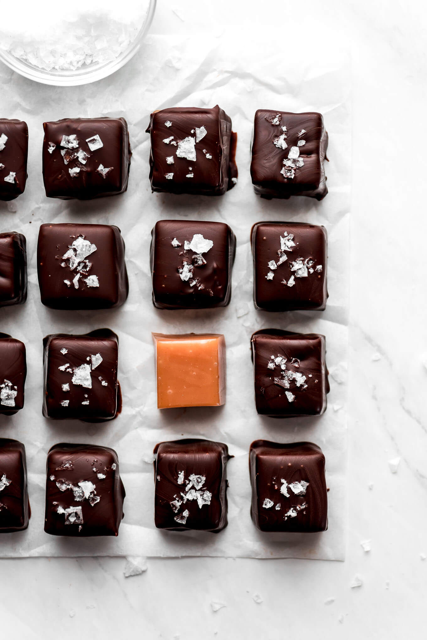 One square of caramel among lots of chocolate coated caramels.