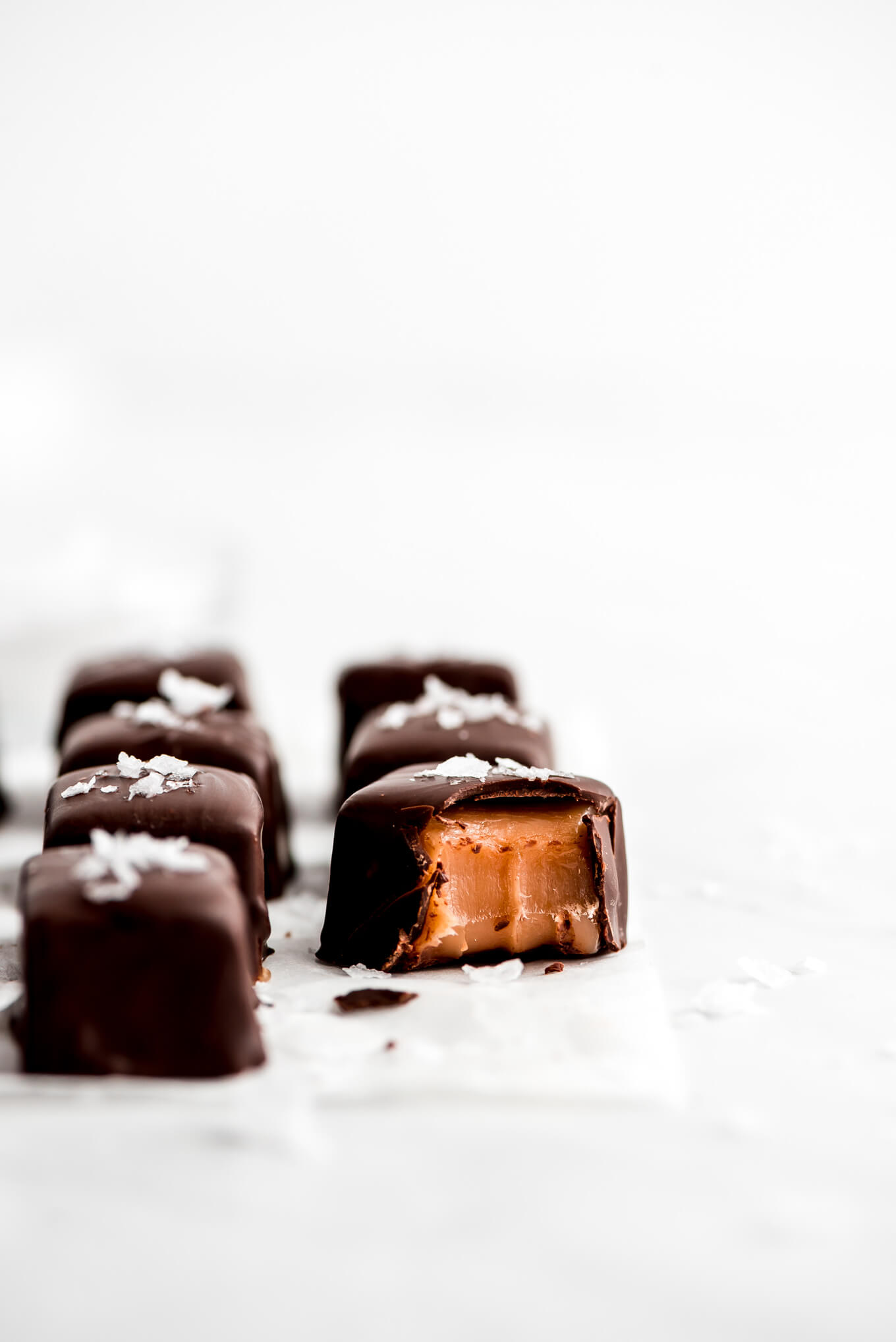 Close up shot of a bitten salted chocolate covered caramel.