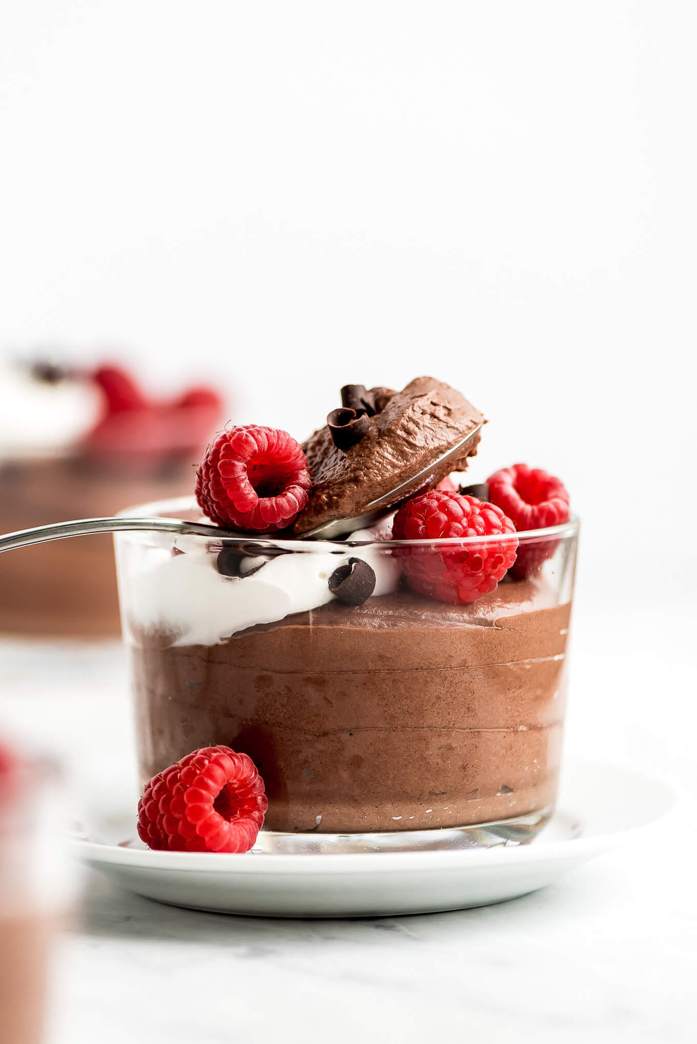 A glass of Chocolate Mousse topped with raspberries, chocolate curls, and whipped cream.