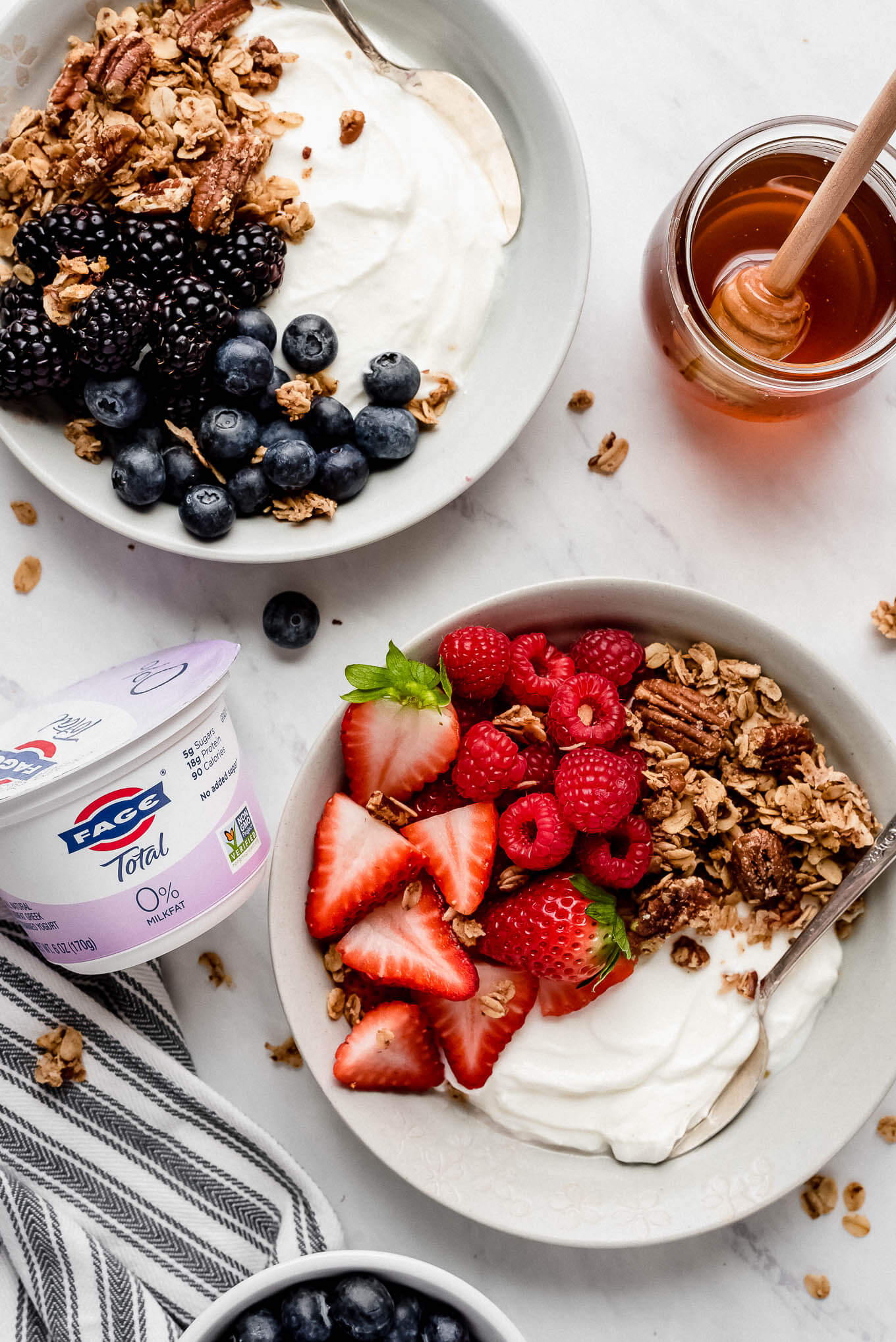 A yogurt bowl with black and blueberries and granola and a yogurt bowl with strawberries, raspberries, and granola.