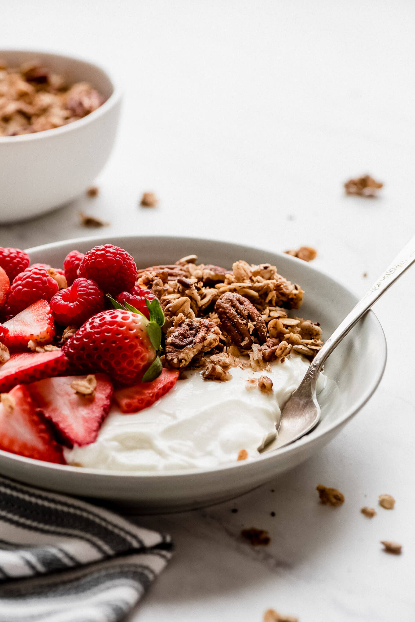 A bowl of Greek yogurt topped with strawberries, raspberries, and granola.