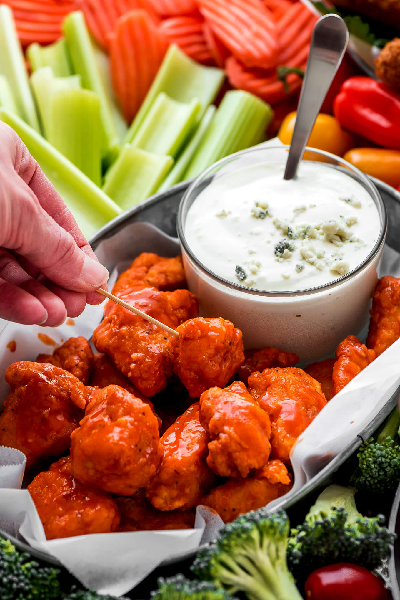 A hand holding a toothpick poking a buffalo chicken bite.