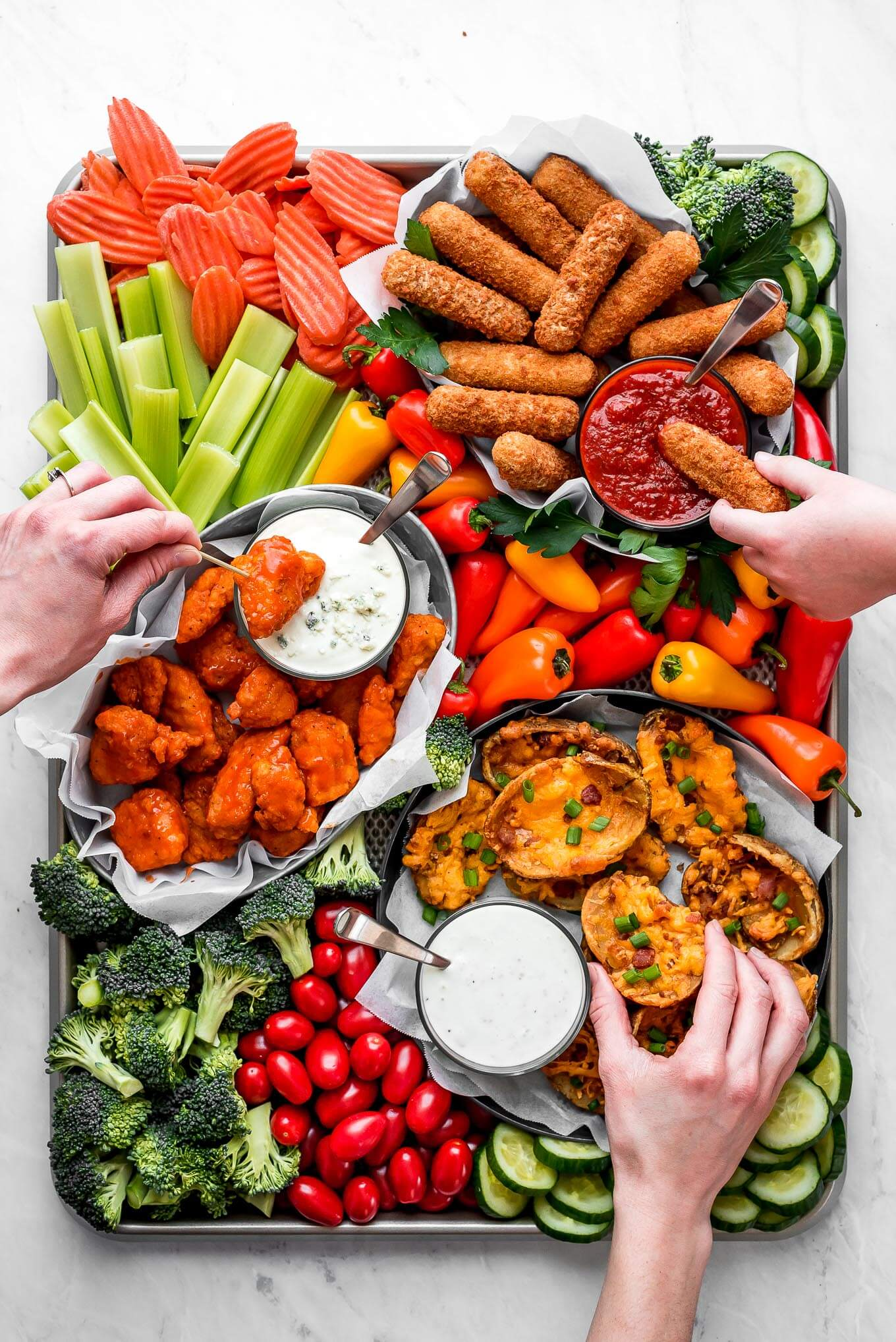 A Super Bowl Snack Board full of fresh vegetables, mozzarella sticks, buffalo, chicken, potato skins, and dipping sauces.