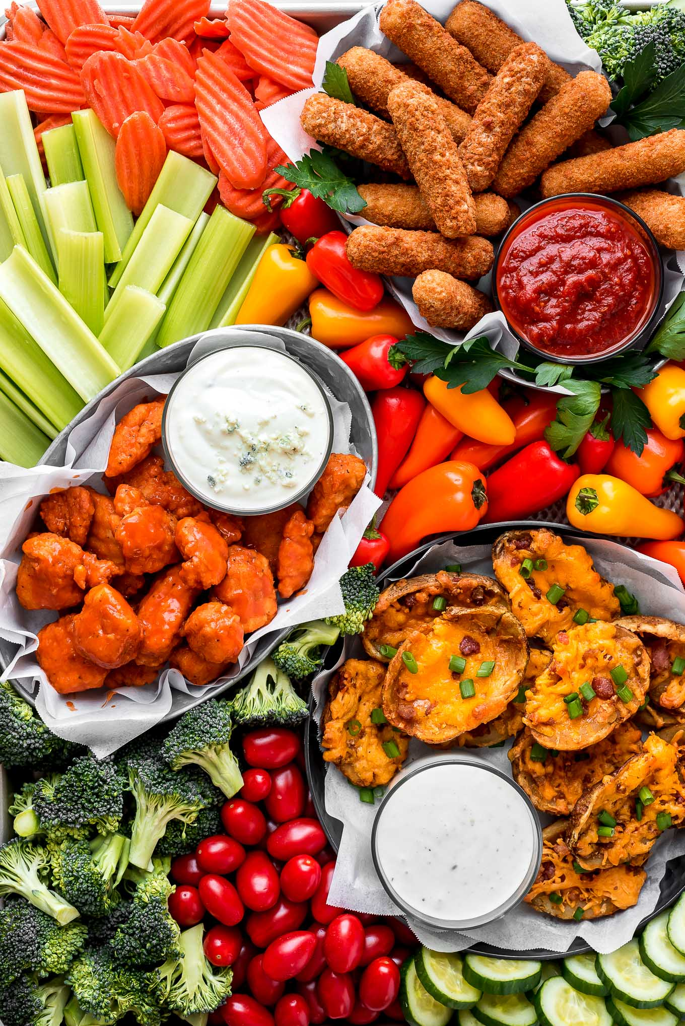 Closeup shot of a Super Bowl Snack Board full of fresh vegetables, mozzarella sticks, buffalo, chicken, potato skins, and dipping sauces.