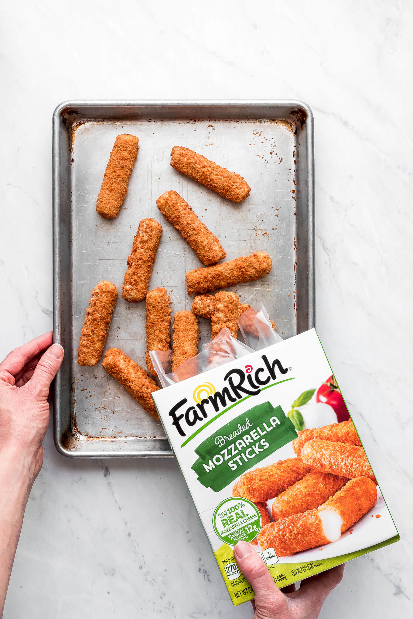 Pouring mozzarella sticks out of a FarmRich box and onto a baking sheet.