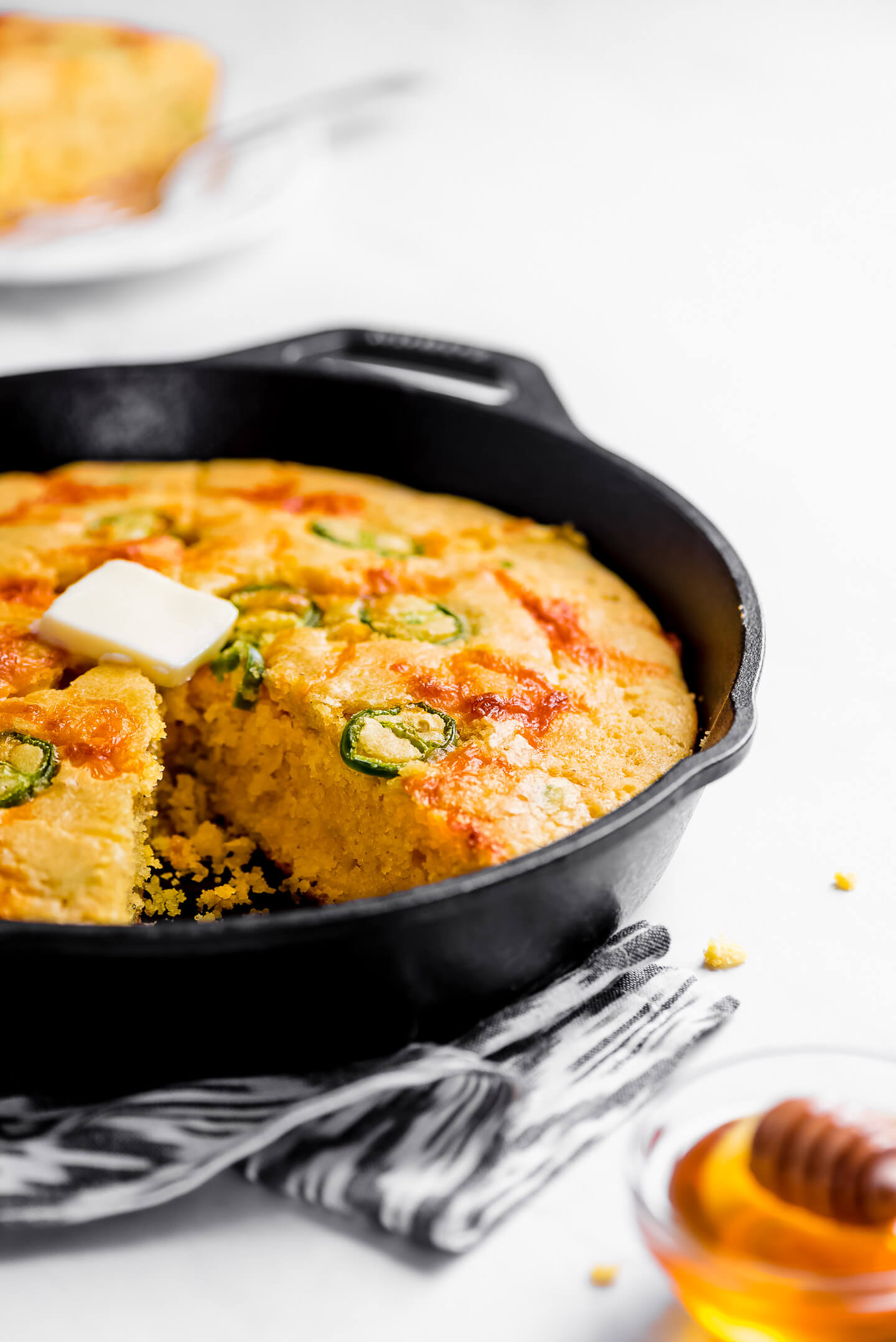 Jalapeno Cornbread in a cast iron skillet with a pat of butter on top and a dish of honey on the side.