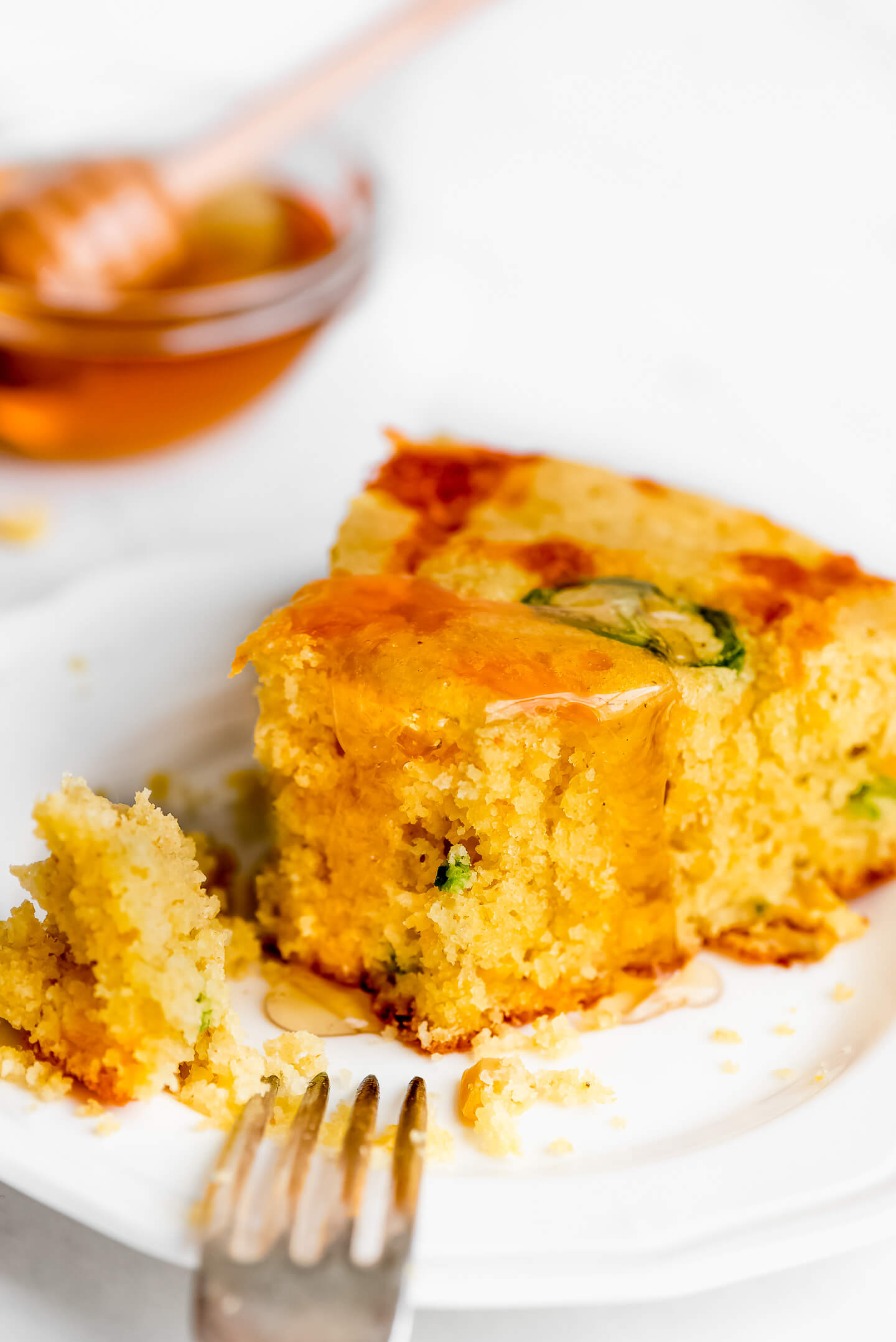 A close-up shot of a slice of Jalapeno Cheddar Cornbread drizzled with honey.