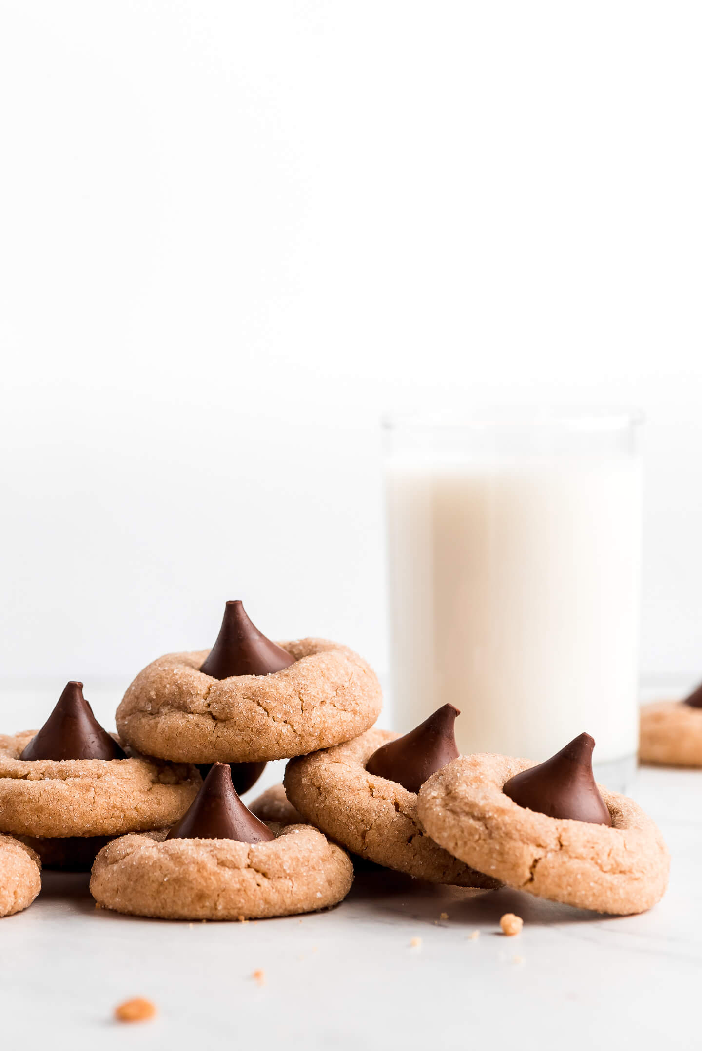 Peanut Butter Kiss cookies stacked in each other and a glass of milk.