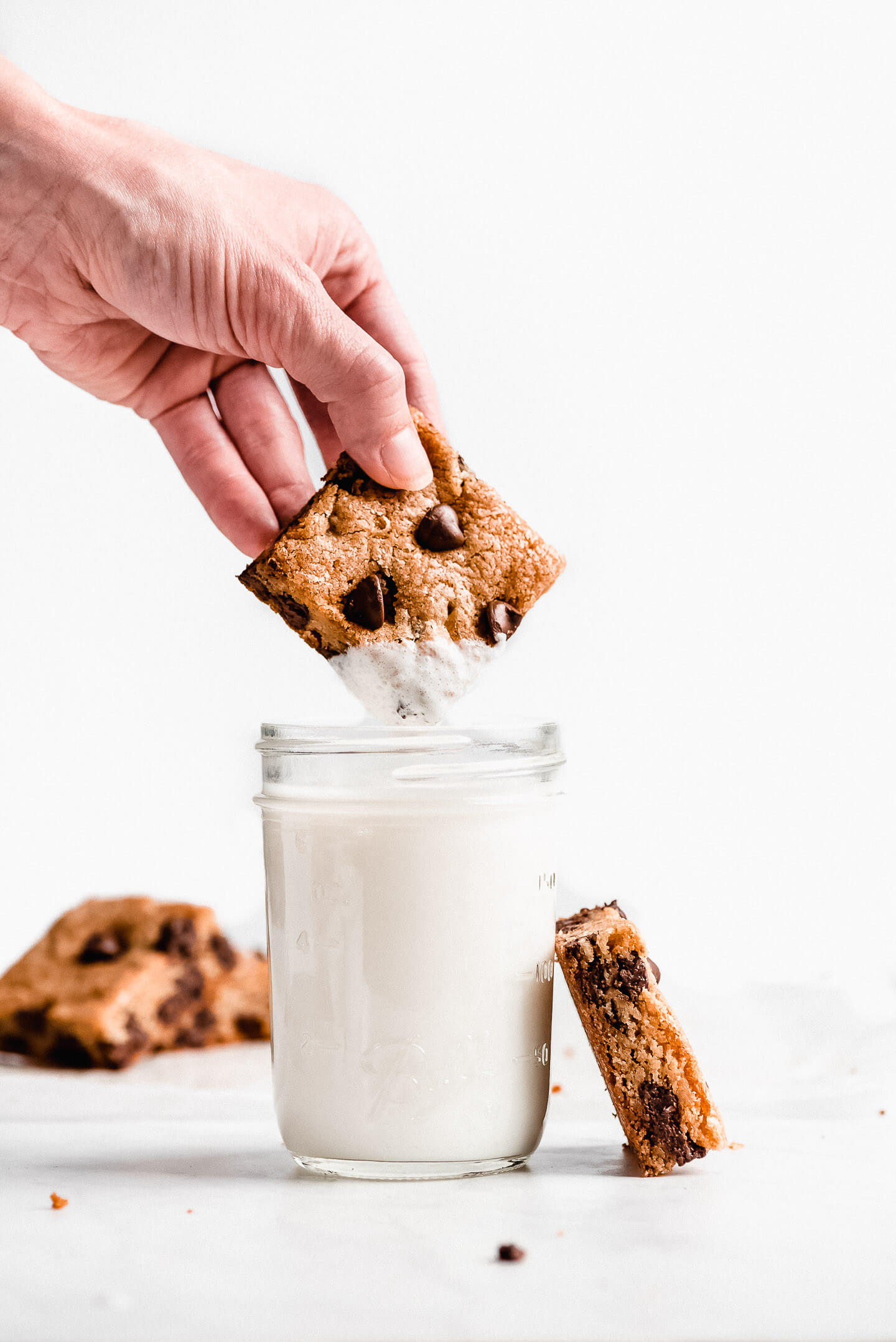 A cookie bar being lifted out of a jar of milk with milk dripping off it.