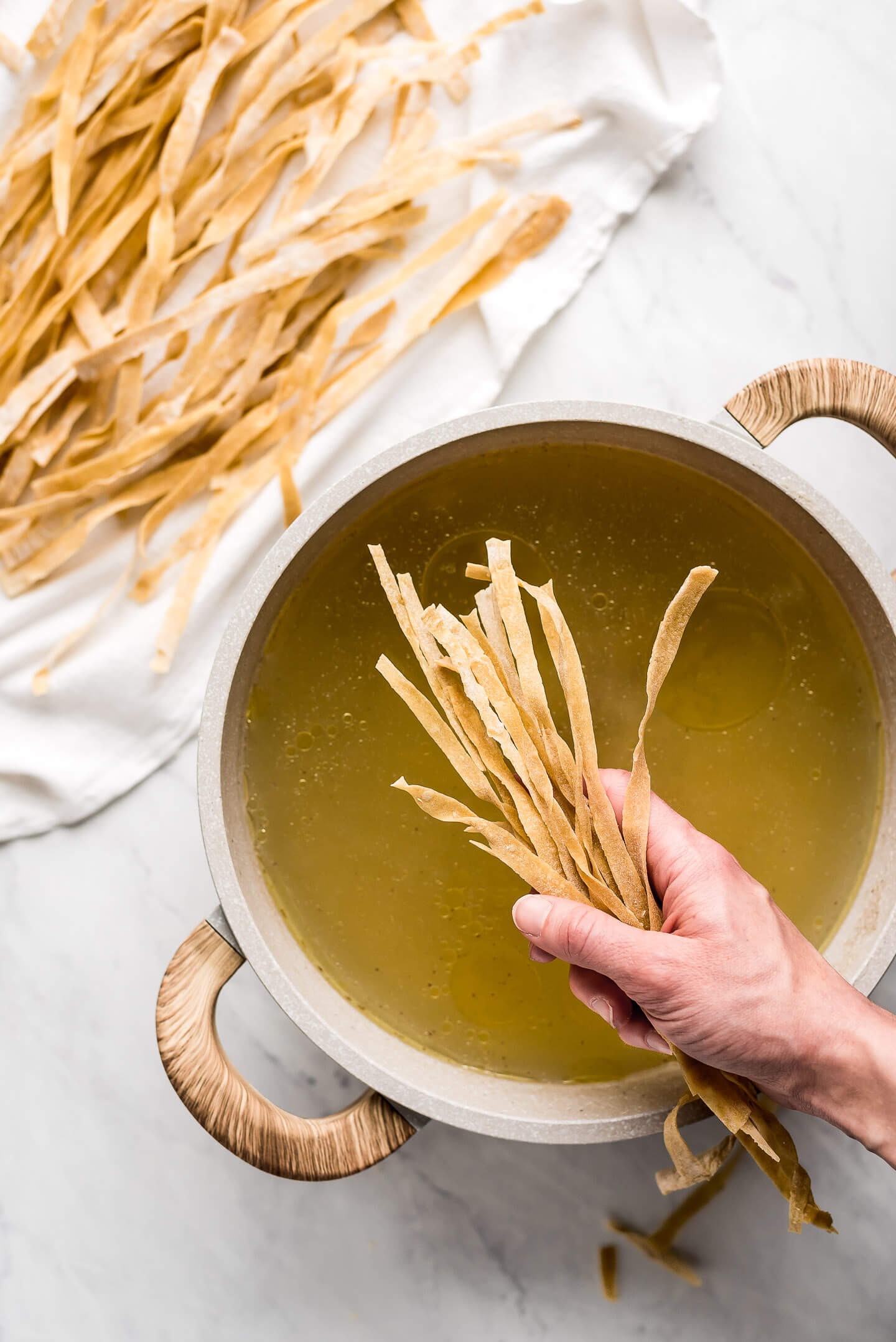 A hand holding a bunch of dried egg noodles over a pot of broth.