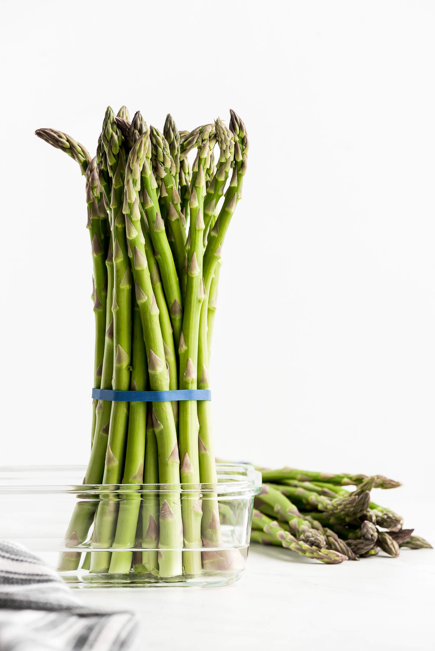 Asparagus spears bundled together with a rubber band and sitting upright in a container of water.