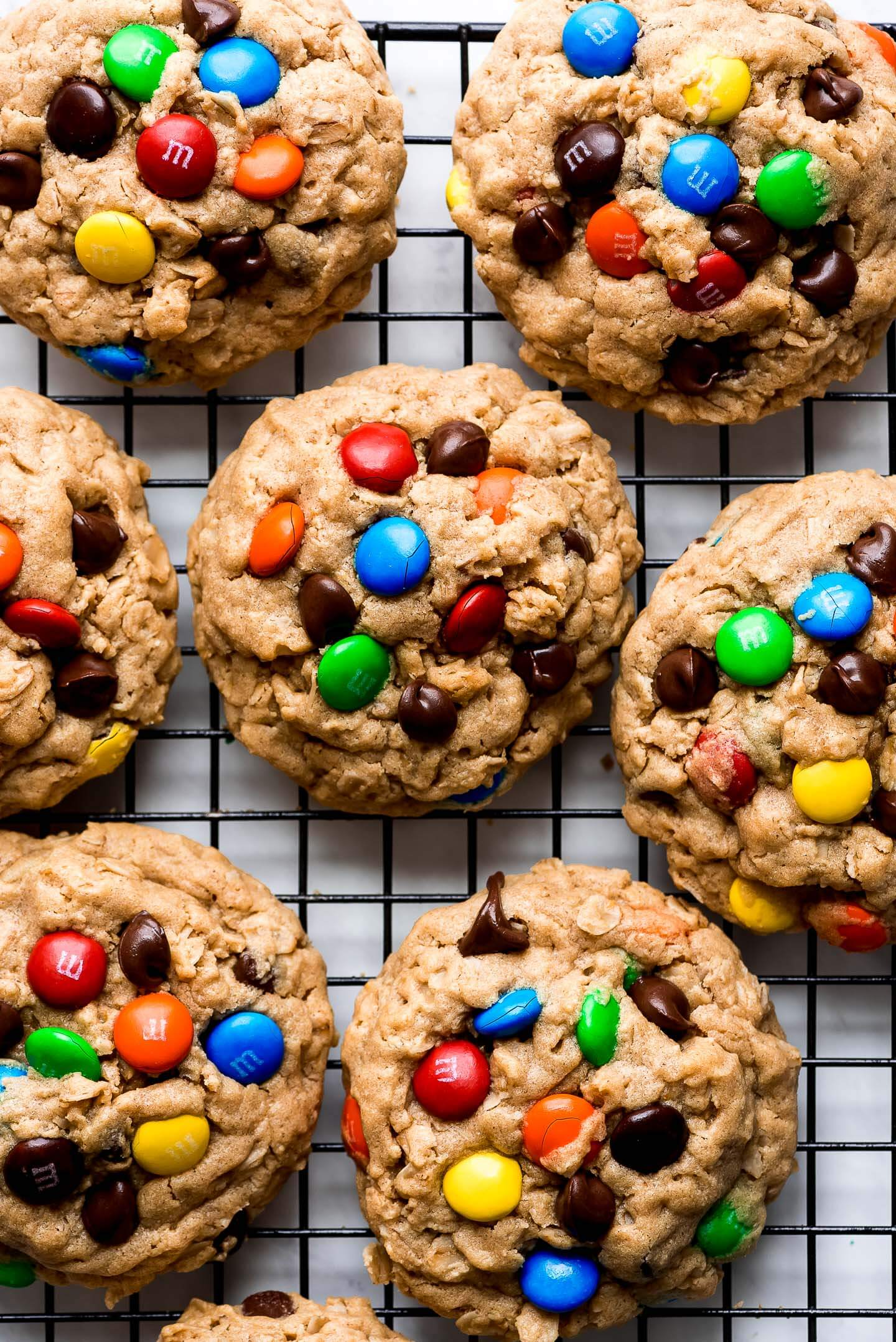 Monster Cookies on a cooking rack topped with chocolate chips and colorful M&M's.