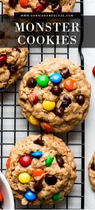 Monster Cookies on a cooling rack with chocolate chips and m&m's pressed into the tops.